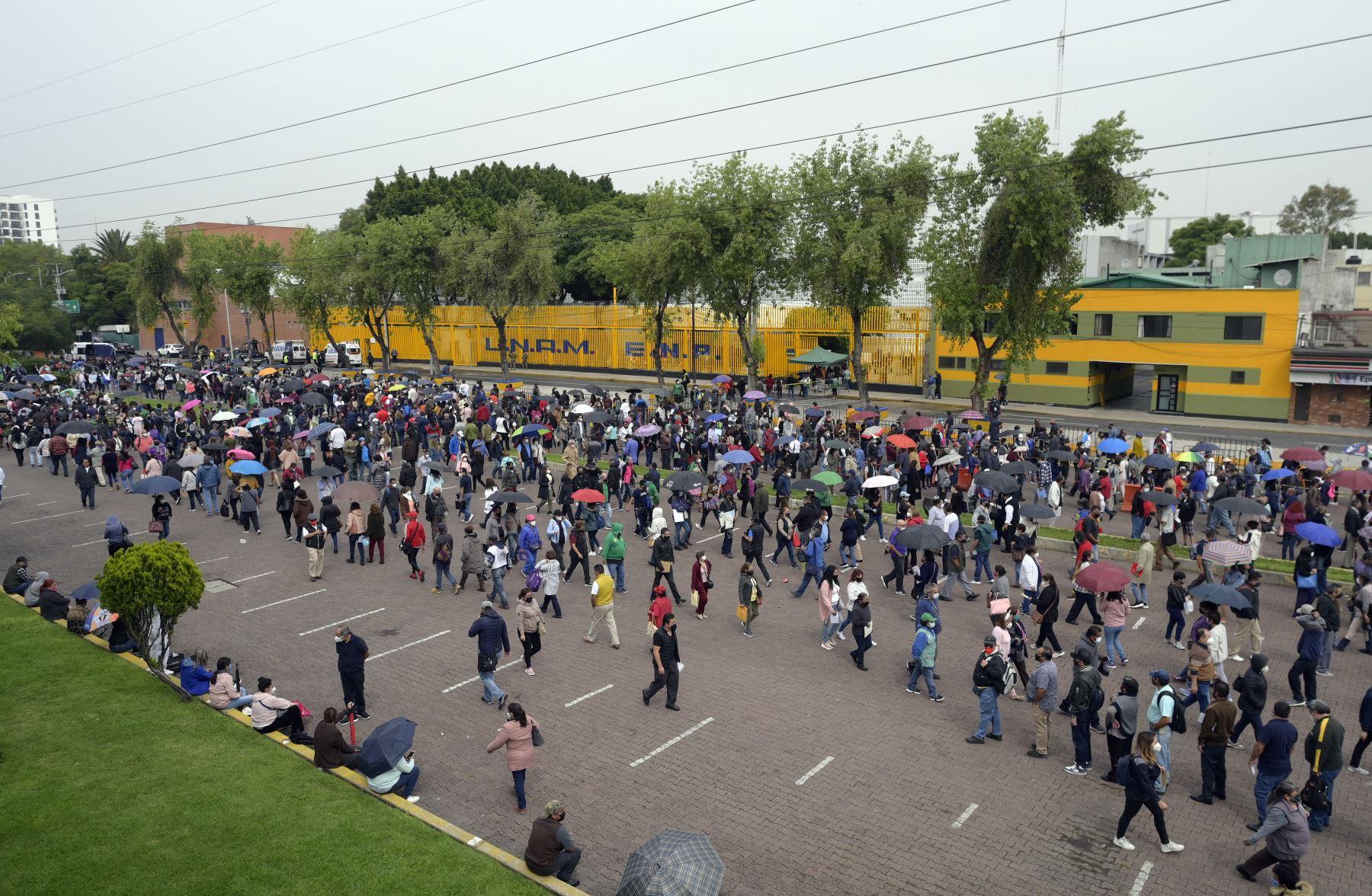 Cientos de personas esperan recibir su primera dosis de la vacuna AstraZeneca / Oxford contra COVID-10 fuera de la Escuela Secundaria No. 9 en la Ciudad de México