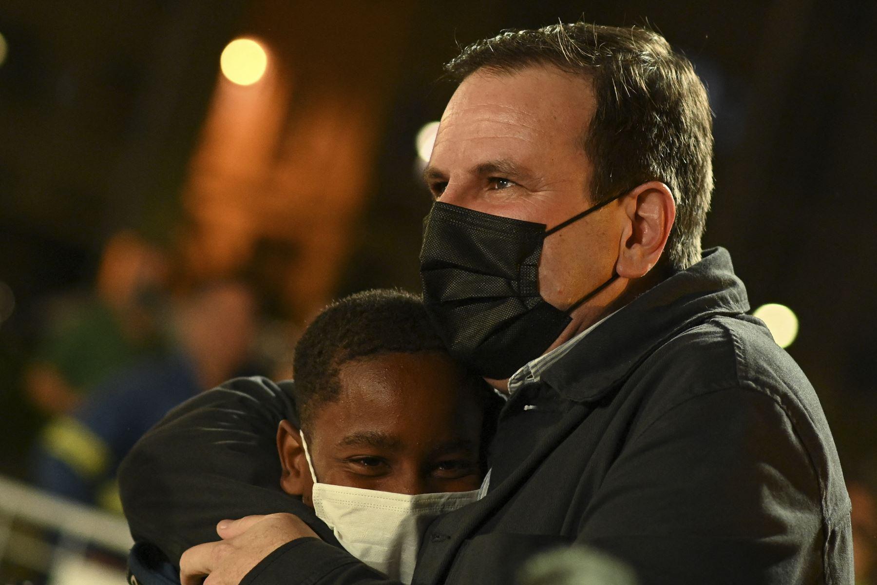El alcalde de Río de Janeiro, Eduardo Paes, abraza a un niño durante una ceremonia donde se iluminó la réplica de la Pira Olímpica Río 2016, frente a la Iglesia de la Candelaria en Río de Janeiro, Brasil. Foto: AFP