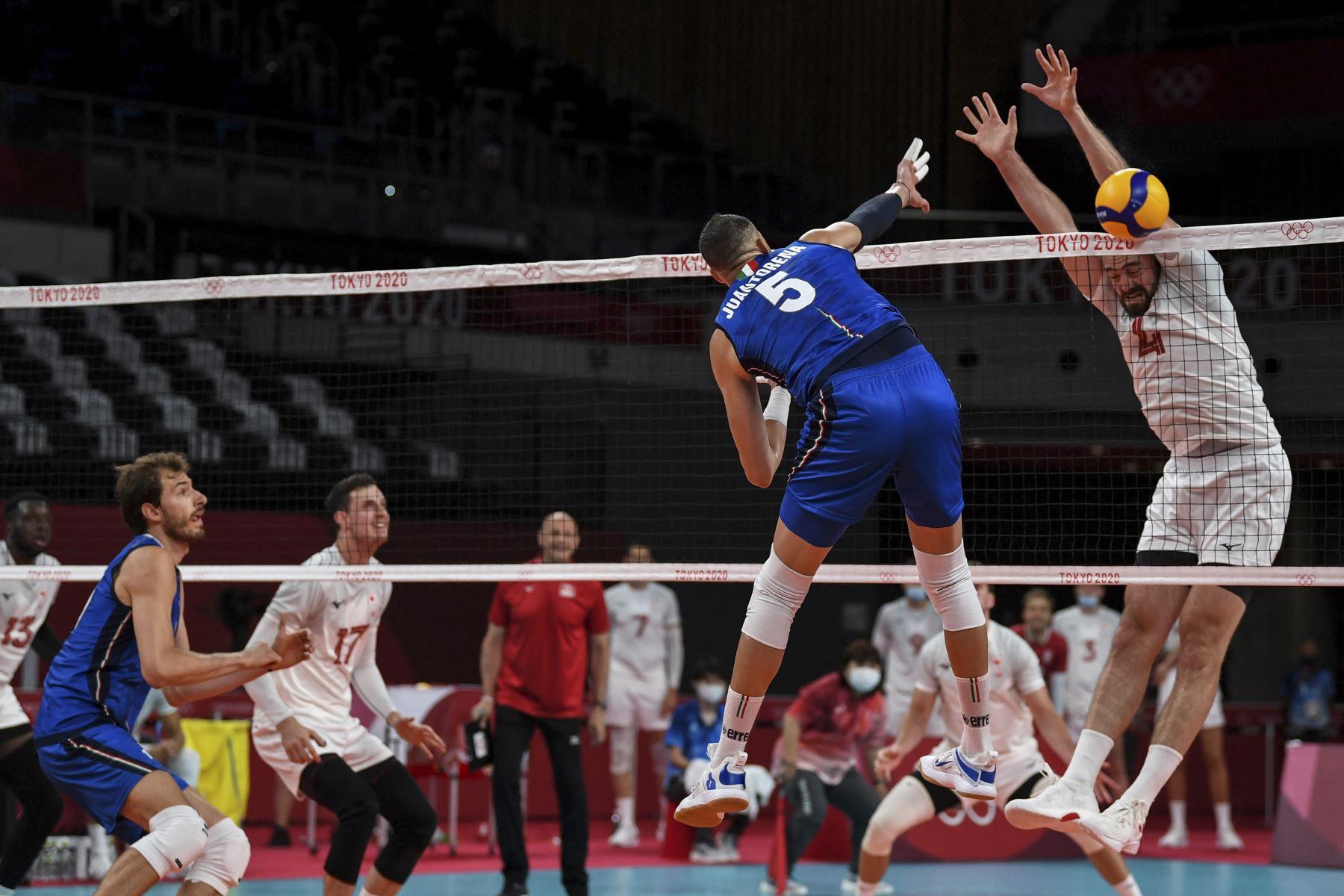 El italiano Osmany Juantorena remata la pelota mientras el canadiense Nicholas Hoag lo bloquea durante partido de voleibol de la ronda preliminar masculina A entre Italia y Canadá por los Juegos Olímpicos de Tokio 2020. Foto: AFP