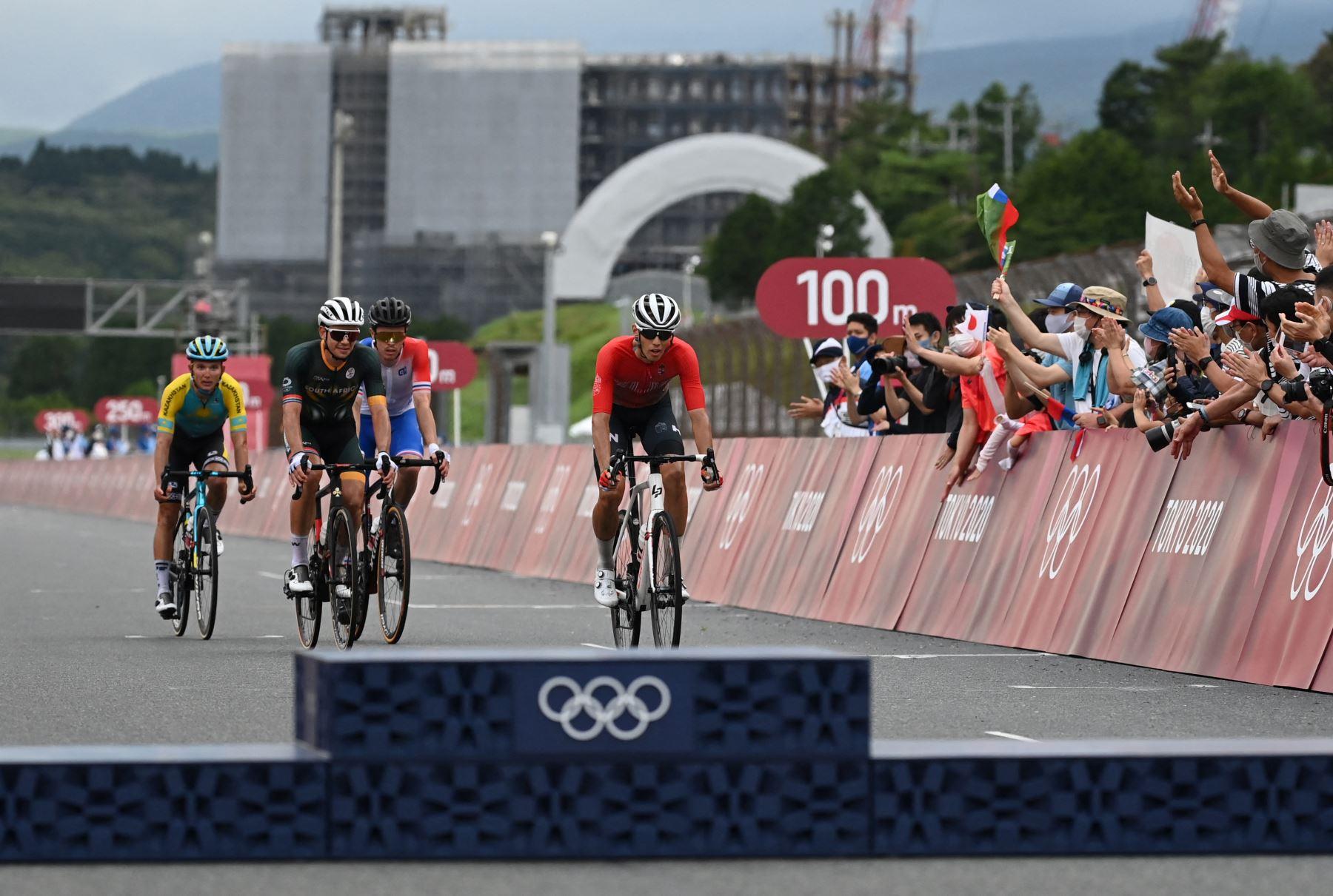 Los finalistas llegan después de la instalación del podio para la ceremonia de entrega de medallas de la carrera de ciclismo en ruta masculino de los Juegos Olímpicos de Tokio 2020, en el Fuji International Speedway en Oyama, Japón. Foto: AFP