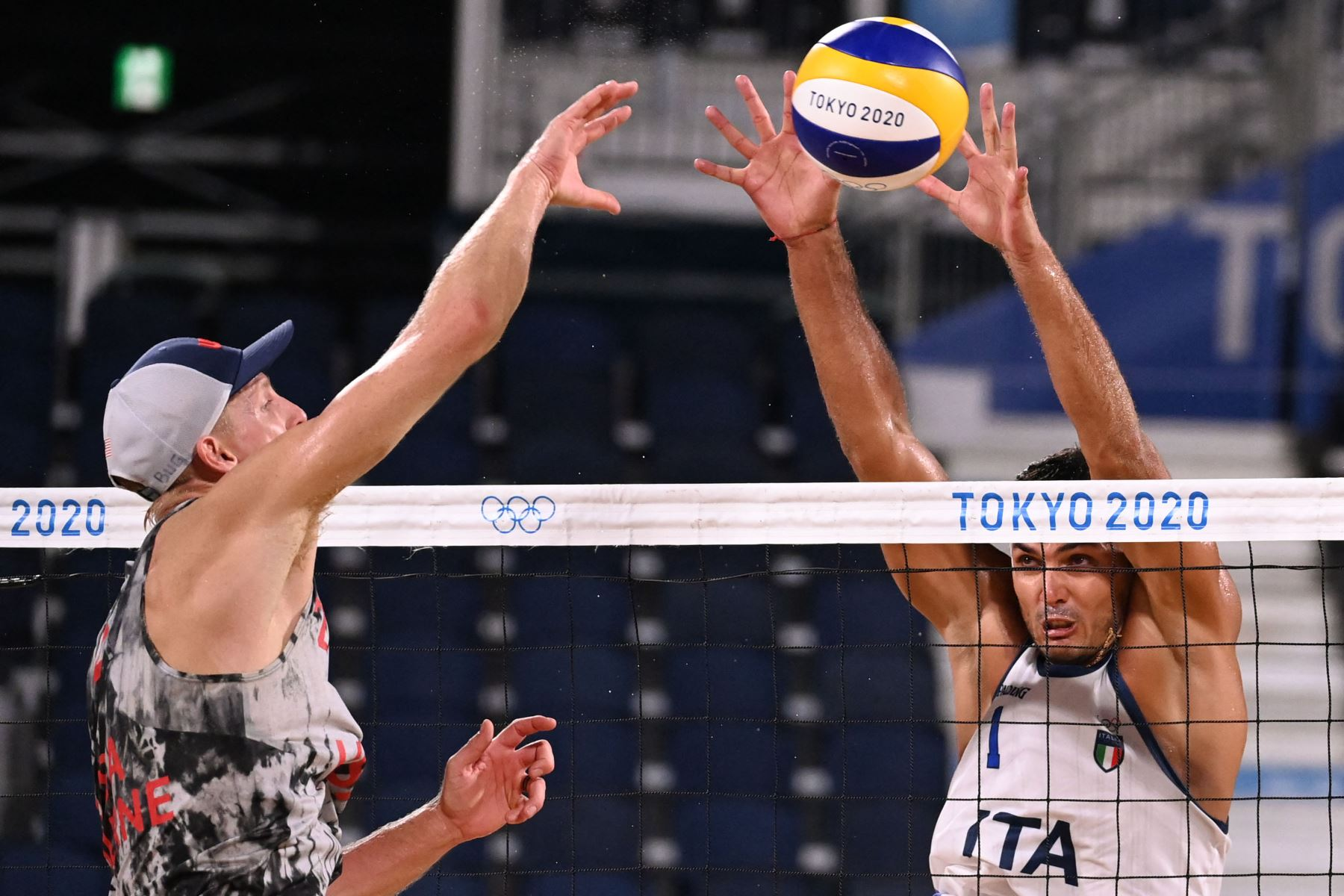 El italiano Enrico Rossi  bloquea un disparo del estadounidense Tri Bourne en el partido preliminar del grupo C de voleibol de playa masculino entre Estados Unidos e Italia durante los Juegos Olímpicos de Tokio 2020. Foto: AFP