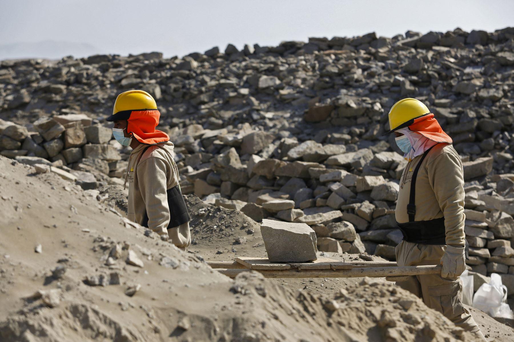 Los trabajadores transportan material durante las obras de recuperación en el Observatorio Solar Chankillo cerca de Casma, Perú. Chankillo, el observatorio solar más antiguo de América entre 500 y 200 a. C., es un complejo de piedra que incluye un templo, plaza y 13 torres alineadas de norte a sur a lo largo de la cima de una colina.  Foto: AFP