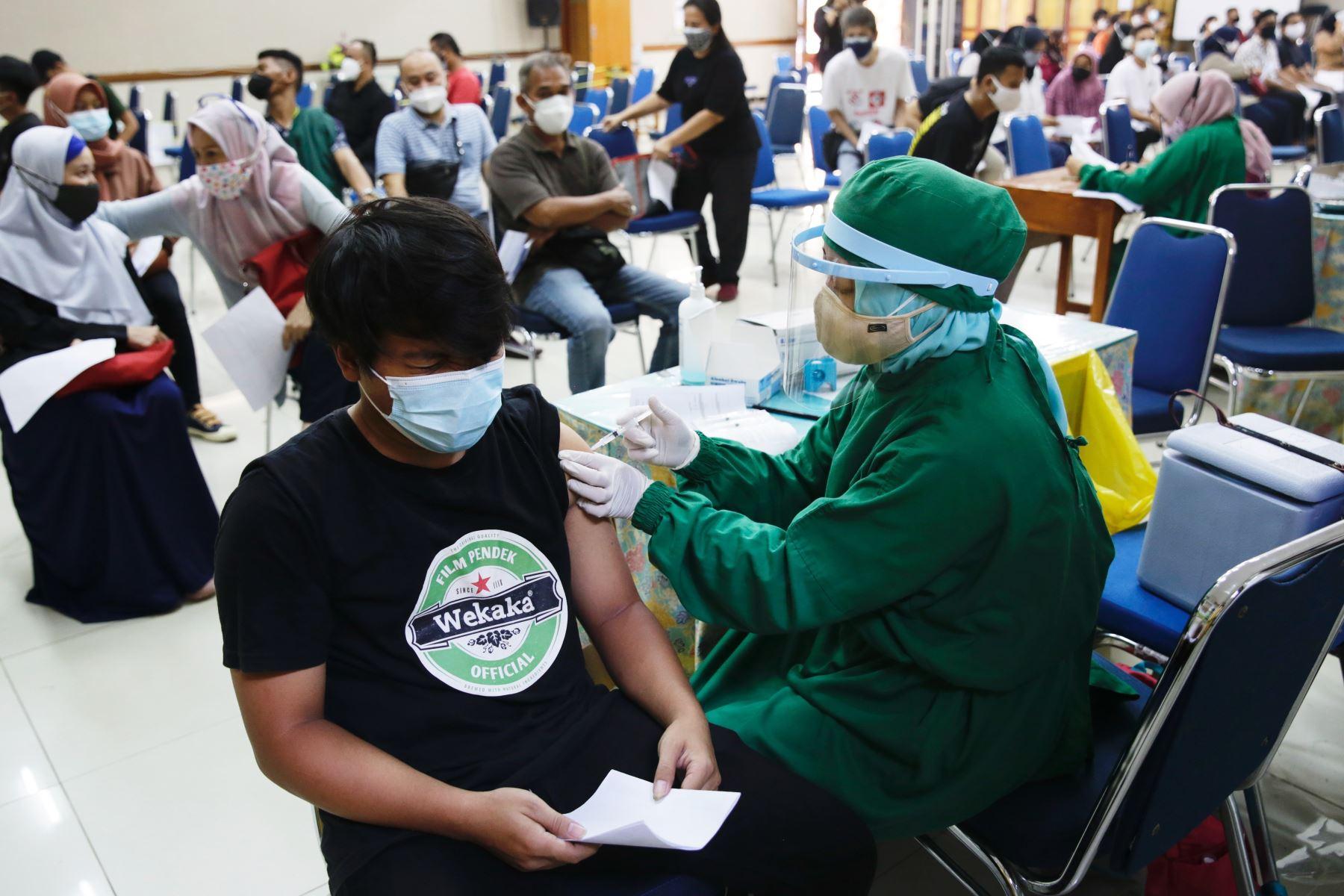 Un estudiante de escuela recibe una dosis de la vacuna COVID-19 durante una campaña masiva en un edificio escolar en Yakarta, Indonesia. Foto: EFE