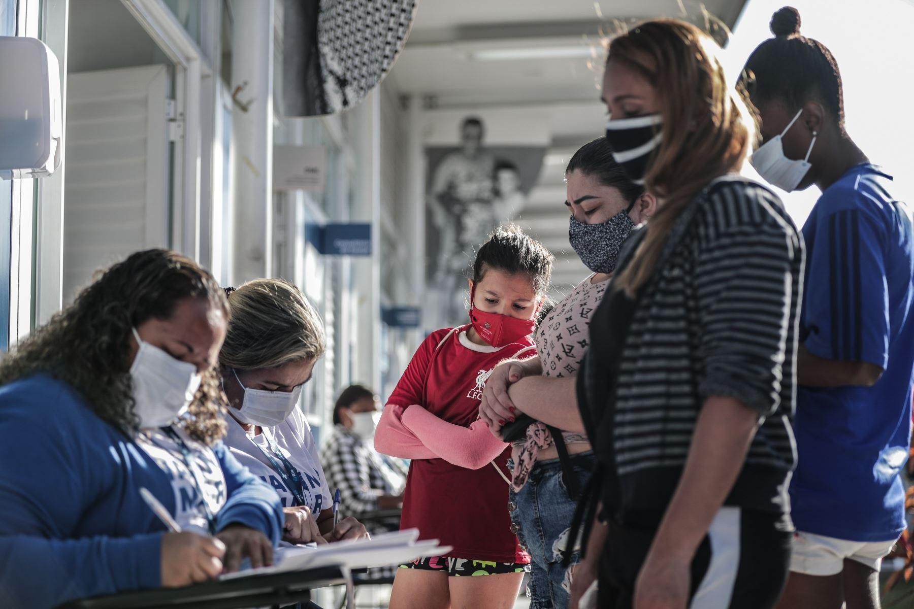 Varias personas asisten a una jornada de vacunación contra la covid-19 en las favelas de Maré, en Rio de Janeiro, Brasil. Foto: EFE