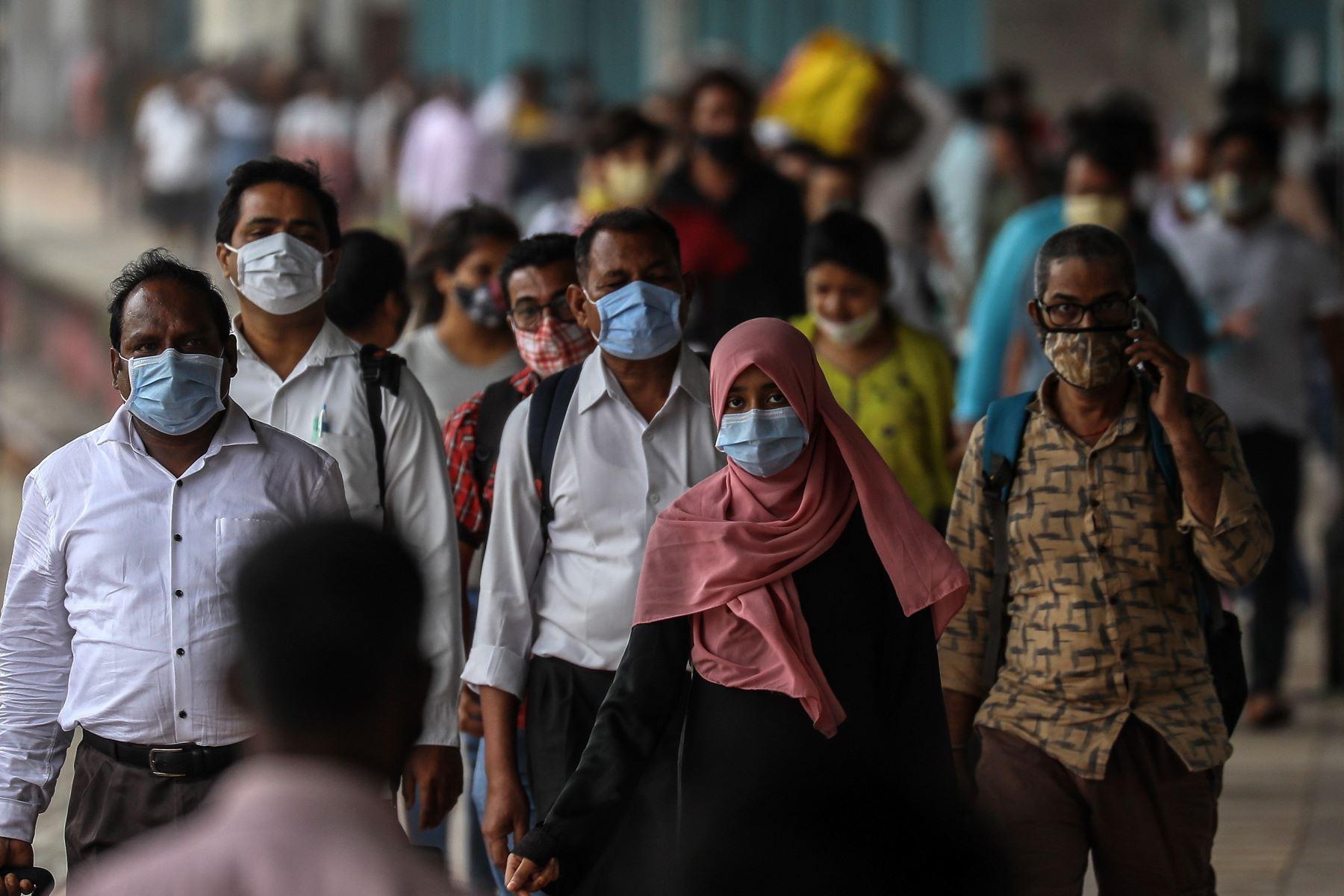 Pasajeros indios con máscaras faciales hacen cola para hacerse la prueba de detección covid-19 después de llegar desde otros estados de la India a Mumbai. Foto: EFE