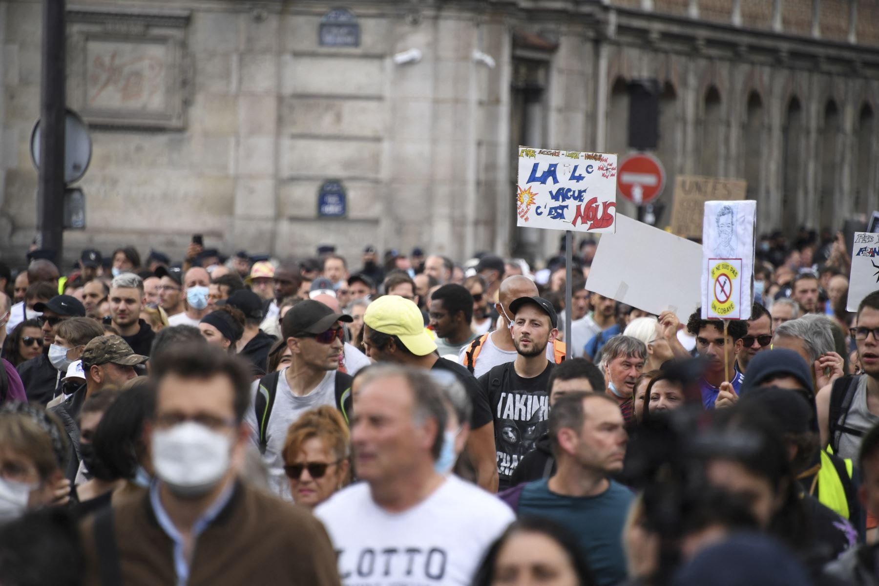 Los manifestantes sostienen pancartas y carteles en contra de la vacunación obligatoria de covid-19, en París, Francia. Foto: AFP