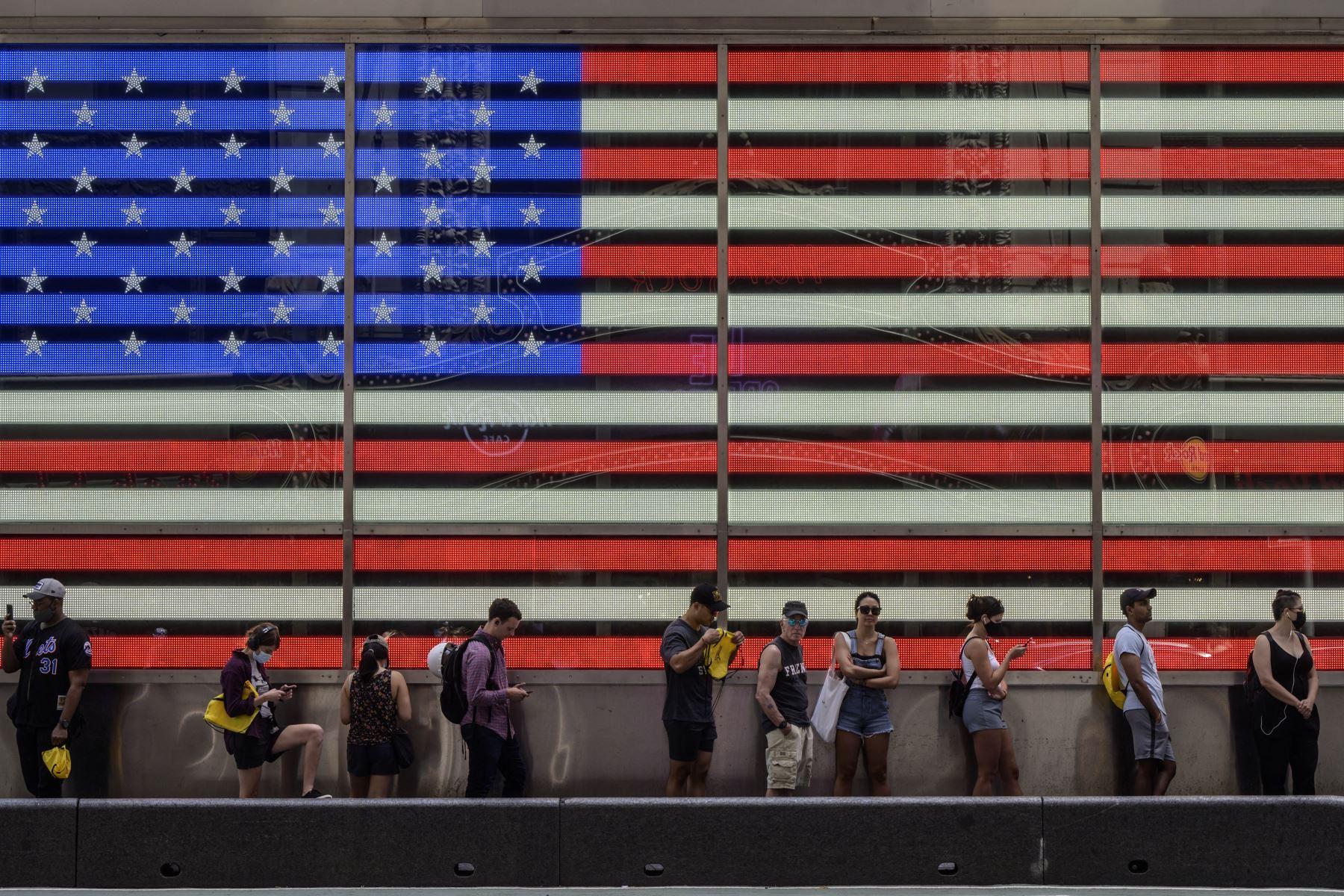 Personas hacen cola tratando de mantener cierta distancia para abordar un autobús turístico antes de una exhibición que muestra la bandera de Estados Unidos, en Times Square, ciudad de Nueva York. Foto: AFP