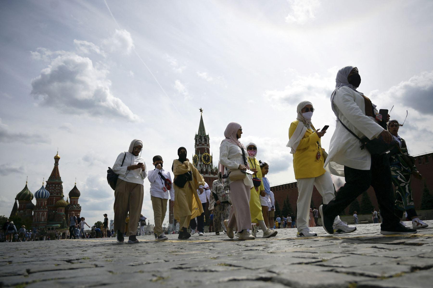 Turistas caminan con mascarillas para protegerse contra la covid-19 por la Plaza Roja en Moscú, Rusia. Foto: AFP