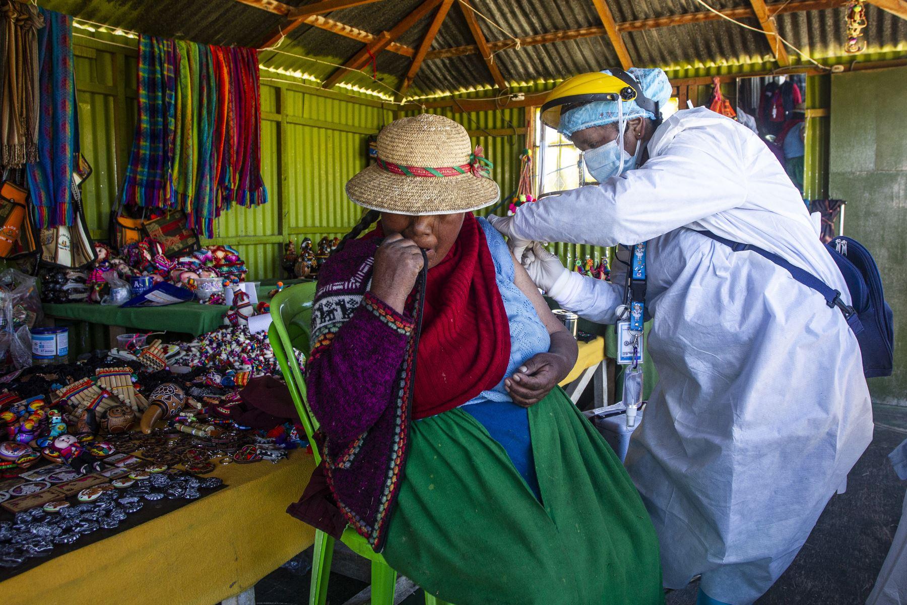 Un trabajador de salud inocula a una mujer con una dosis de la vacuna Sinopharm contra la covid-19, en las islas de los Uros, en el lago Titicaca, en Puno. Foto: AFP