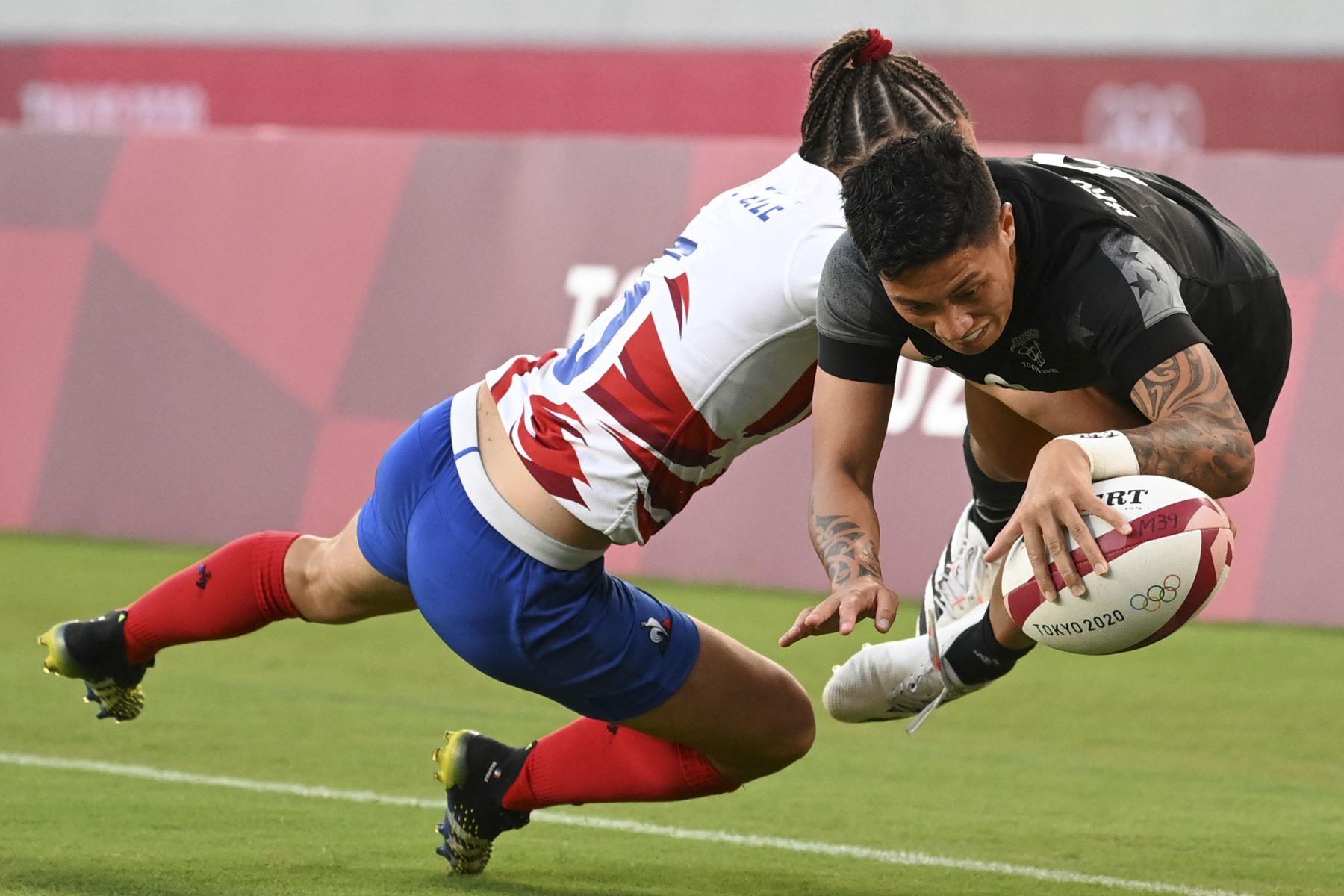 Gayle Broughton de Nueva Zelanda anota un try a pesar de una entrada de la francesa Jade Ulutule en el último partido femenino de rugby durante los Juegos Olímpicos de Tokio 2020. Foto: AFP