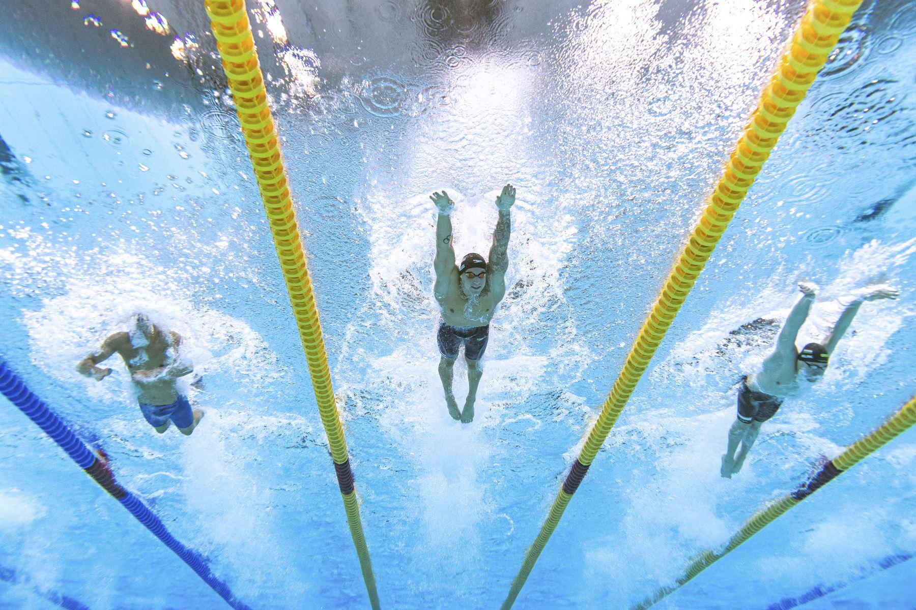 Una vista submarina muestra al húngaro Kristof Milak, el estadounidense Caeleb Dressel y el suizo Noe Ponti, mientras compiten en la final de natación estilo mariposa - 100 metros, durante los Juegos Olímpicos de Tokio 2020, en el Centro Acuático de Tokio. Foto: AFP