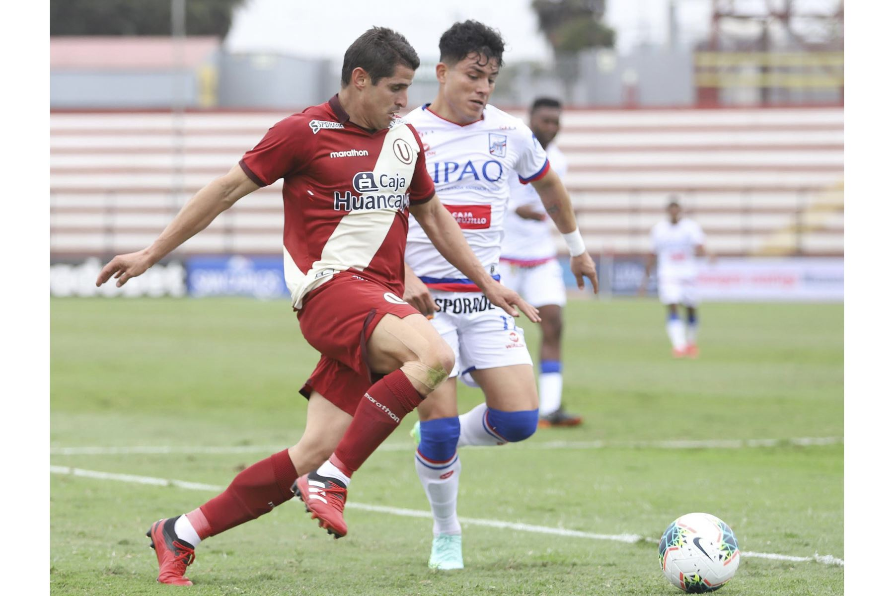 Aldo Corzo de Universitario disputa el balón ante la marca de su rival de Carlos Manucci durante partido por la tercera fecha de la Liga 1, en el Estadio Miguel Grau. Foto: Liga 1