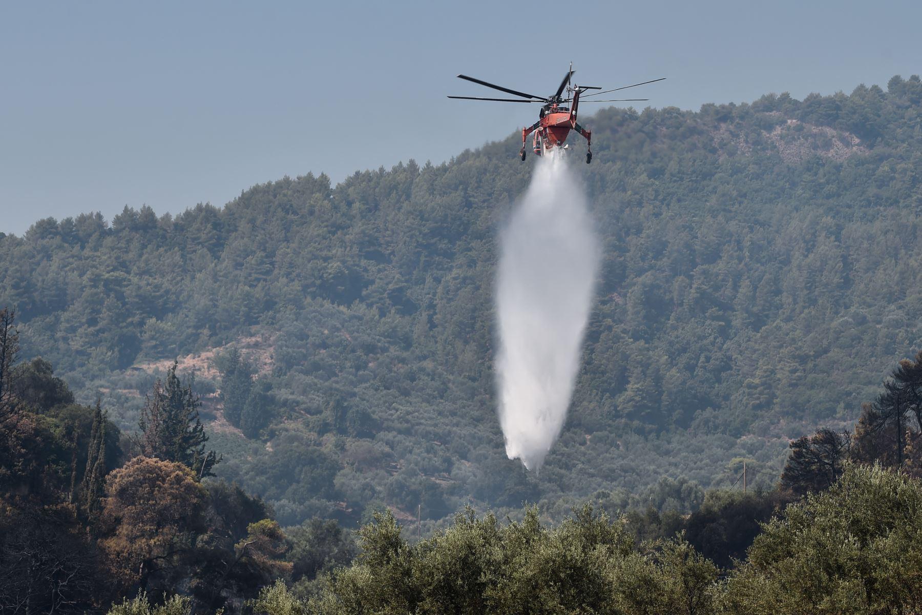 Un helicóptero Sikorsky S-64 Skycrane deja caer su carga de agua mientras lucha contra incendios en Ziria, cerca de Patras. Cerca de 300 bomberos, dos aviones bombarderos de agua y cinco helicópteros estaban luchando para apagar un incendio forestal en Grecia. Foto: AFP