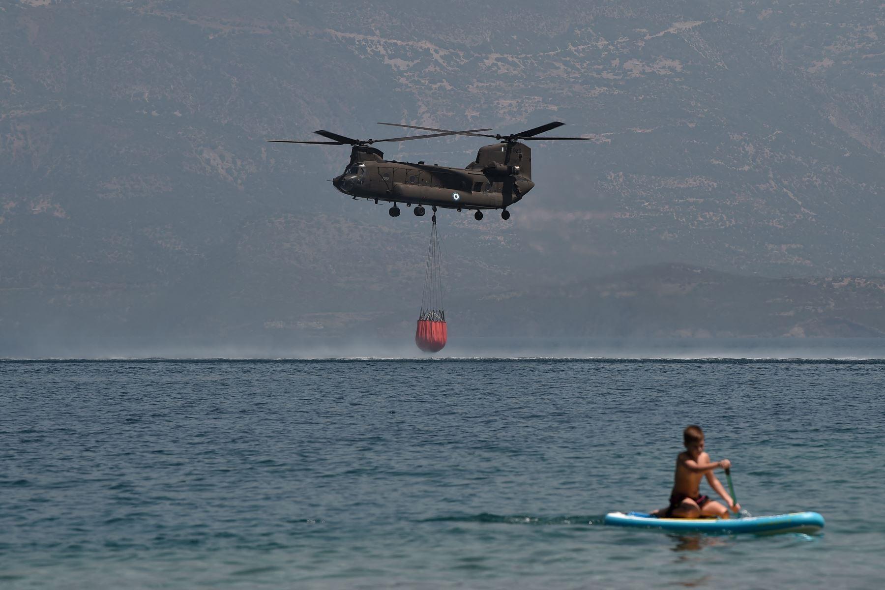Un helicóptero Ch-47D Chinook es observado por un bañista mientras se llena de agua para apagar incendios cerca de la playa Lambiri en Patras. Foto : AFP