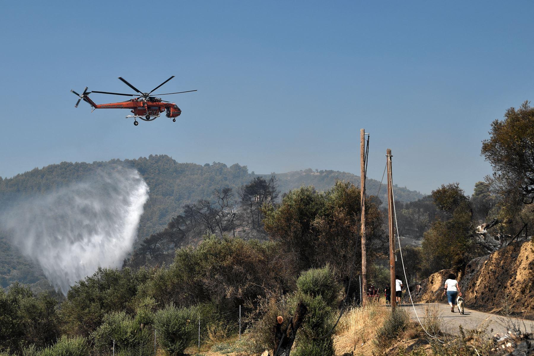 Un helicóptero Sikorsky S-64 Skycrane deja caer su carga de agua mientras lucha contra incendios en Ziria, cerca de Patras. Foto: AFP