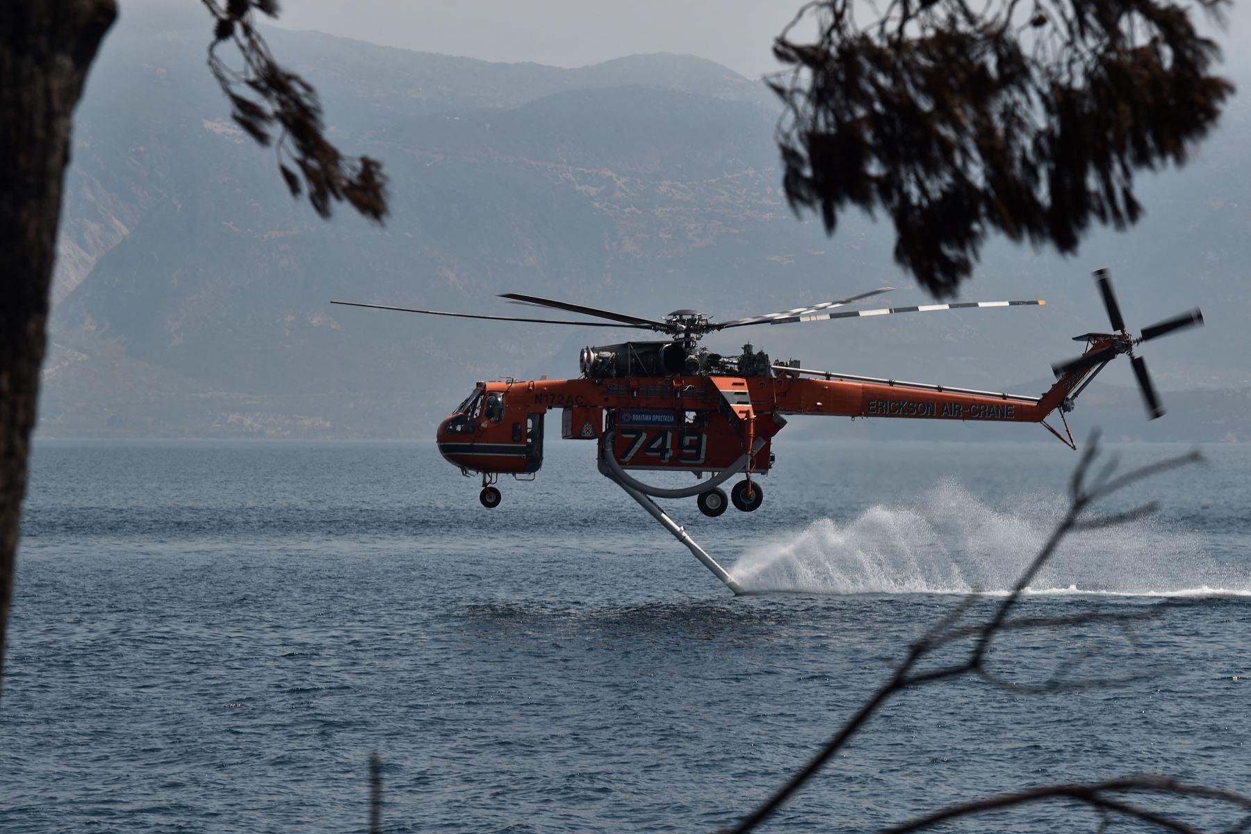 Un helicóptero Sikorsky S-64 Skycrane regresa al océano para llenarse de agua mientras lucha contra incendios cerca de la playa Lambiri cerca de Patras en Grecia.  Foto : AFP