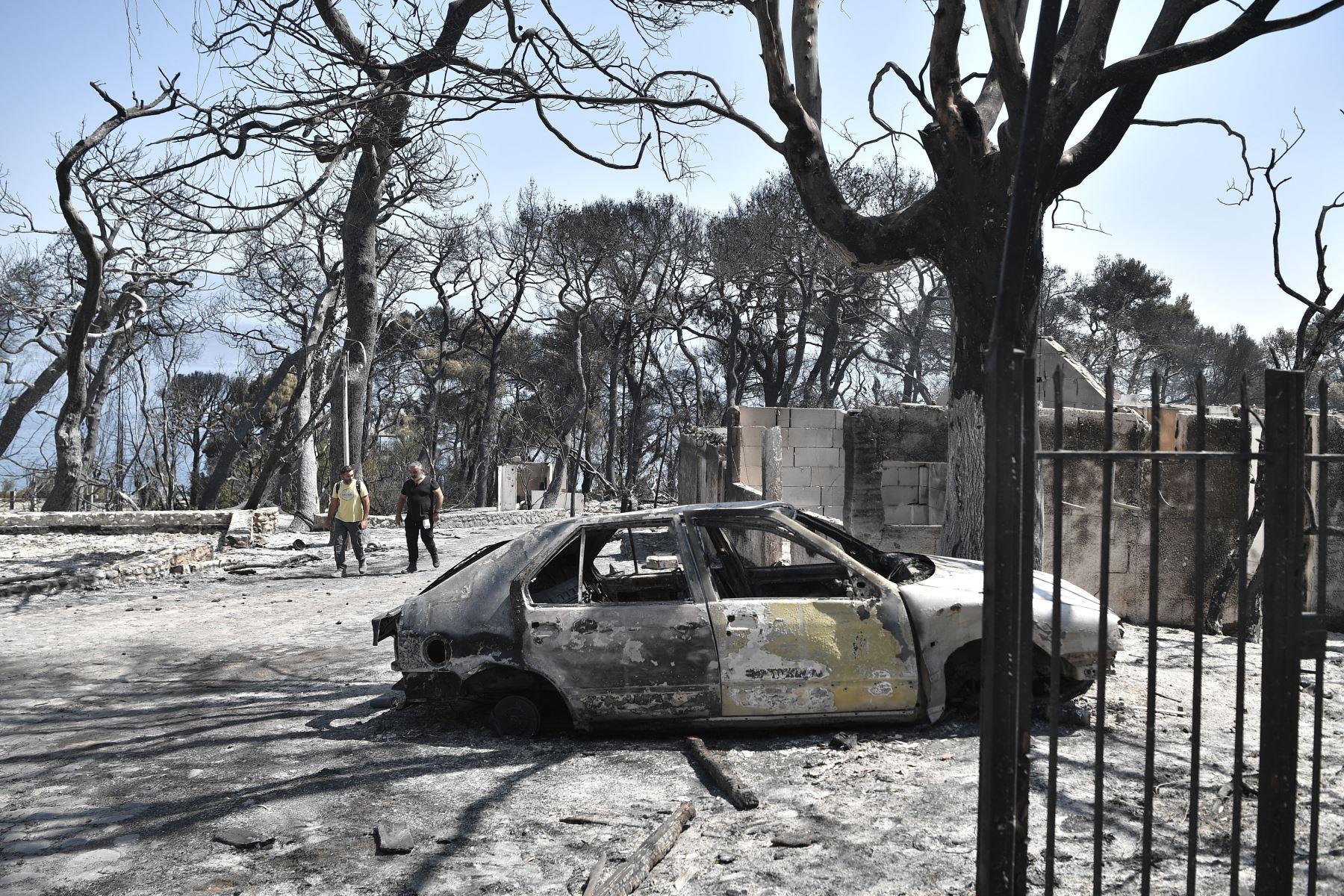 Los residentes locales caminan en el área quemada de un Club Mediterranee abandonado en Lambiri, al este de Patras en Grecia.  Foto: AFP