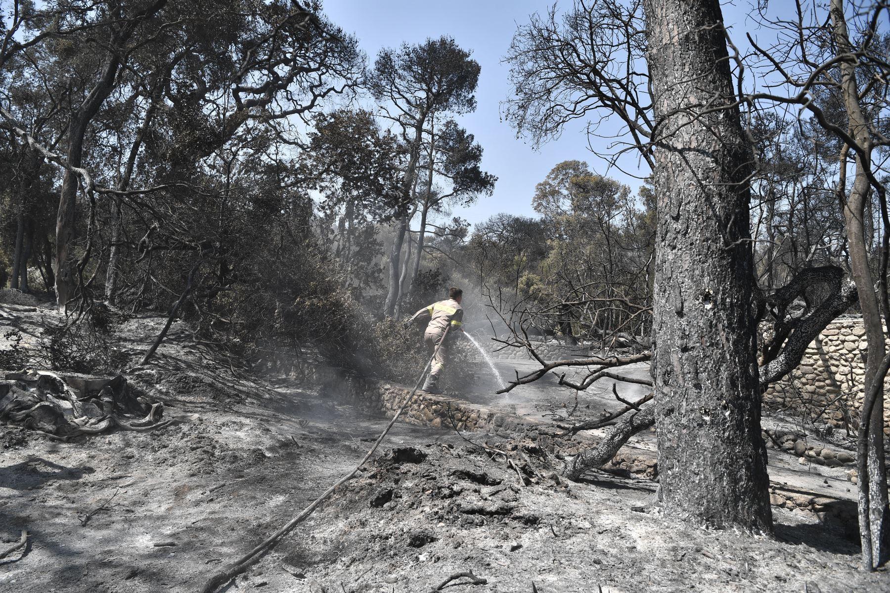 Un bombero limpia el trabajo en el área quemada de un Club Mediterranee abandonado en Lambiri, al este de Patras. Foto: AFP