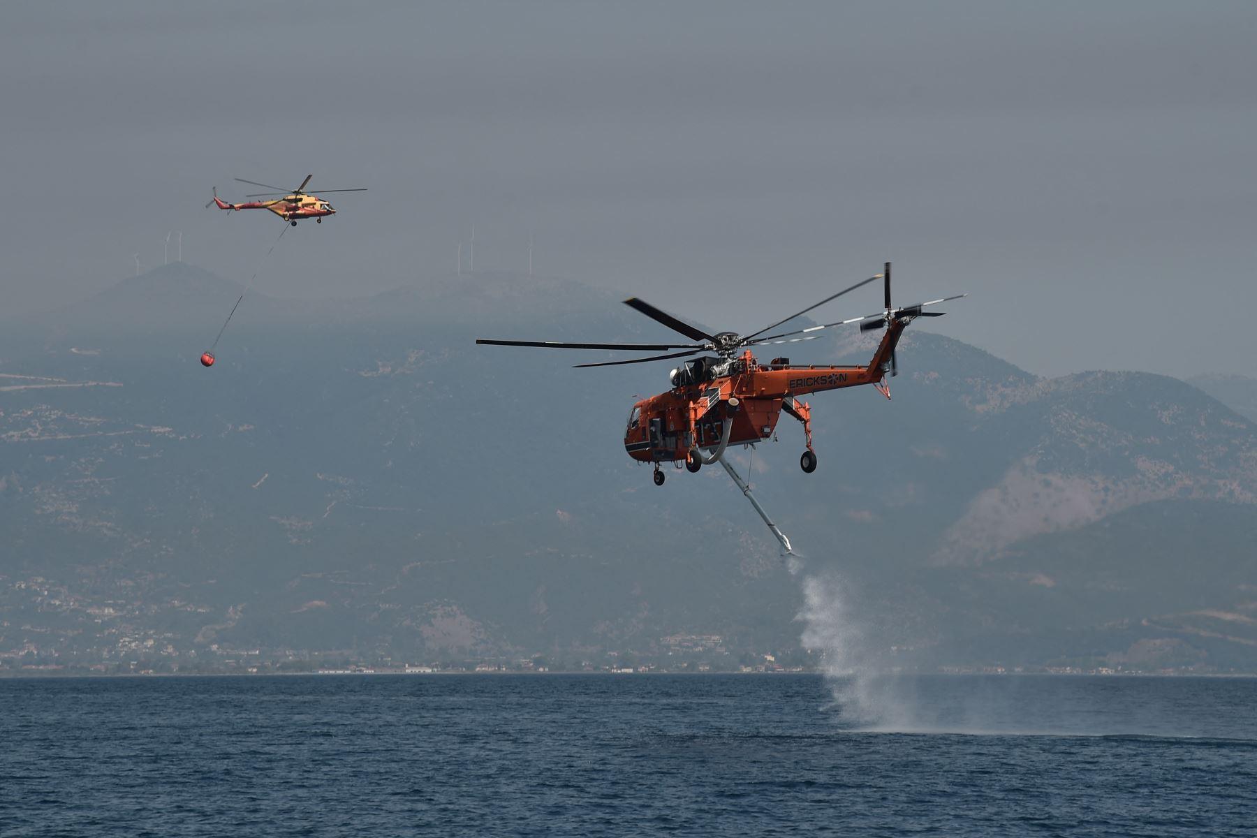 Un helicóptero Sikorsky S-64 Skycrane se llena de agua mientras lucha contra incendios cerca de la playa Lambiri en Patras en Grecia. Foto: AFP