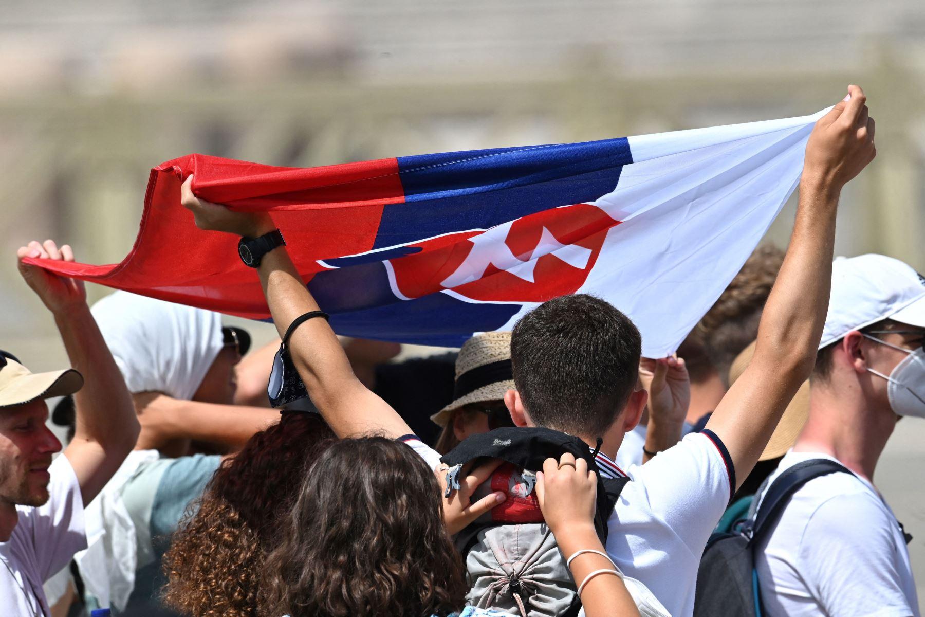 Los peregrinos eslovenos sostienen su bandera nacional mientras el Papa Francisco pronuncia la oración del Ángelus dominical desde la ventana de su estudio con vista a la Plaza de San Pedro en el Vaticano. Foto: AFP