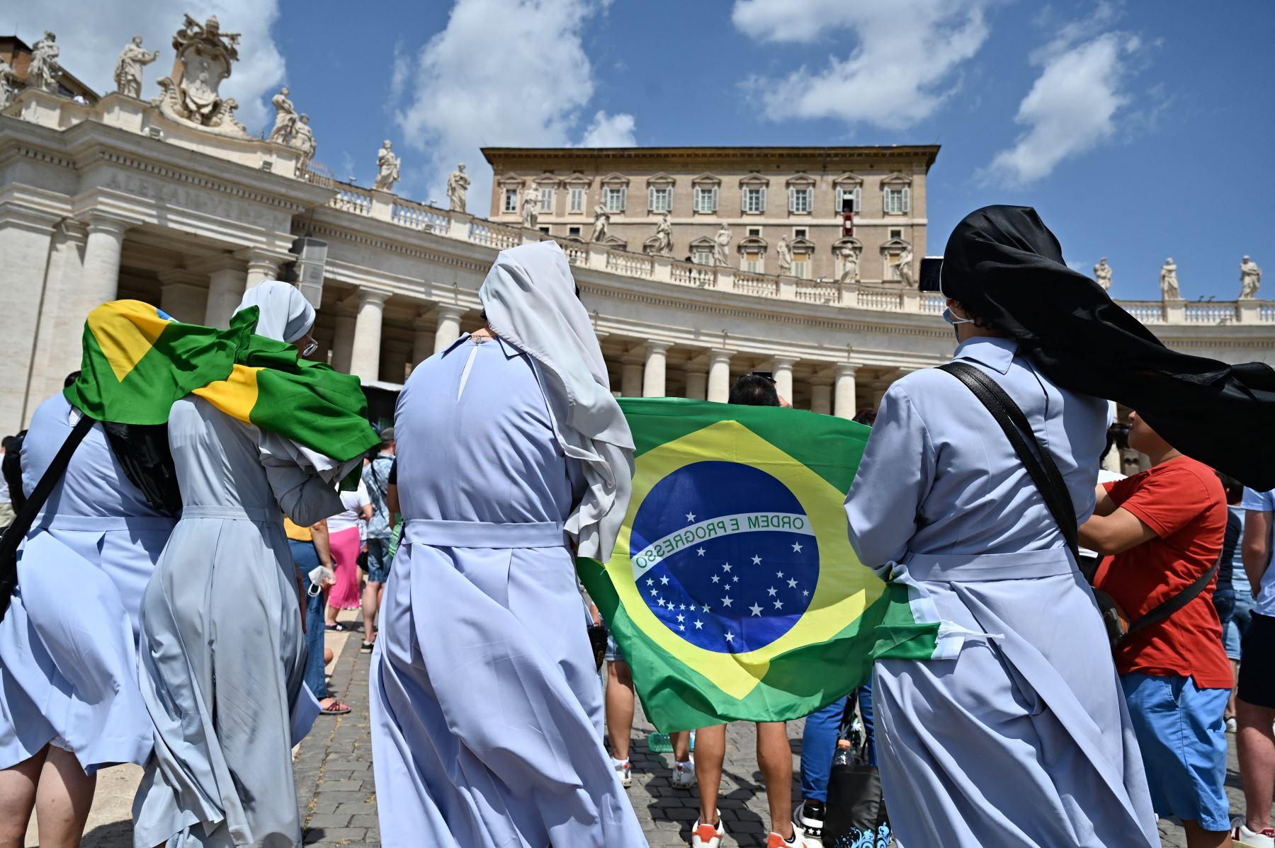 Las monjas sostienen una bandera brasileña mientras el Papa Francisco pronuncia la oración del Ángelus dominical desde la ventana de su estudio con vista a la Plaza de San Pedro en el Vaticano. Foto: AFP
