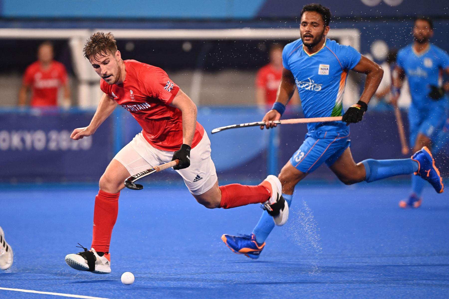 El británico Liam Paul Ansell lleva el balón al lado de Harmanpreet Singh de la India durante su partido de cuartos de final masculino de la competencia de hockey sobre césped de los Juegos Olímpicos de Tokio 2020, en el Estadio de Hockey Oi en Tokio. Foto: AFP