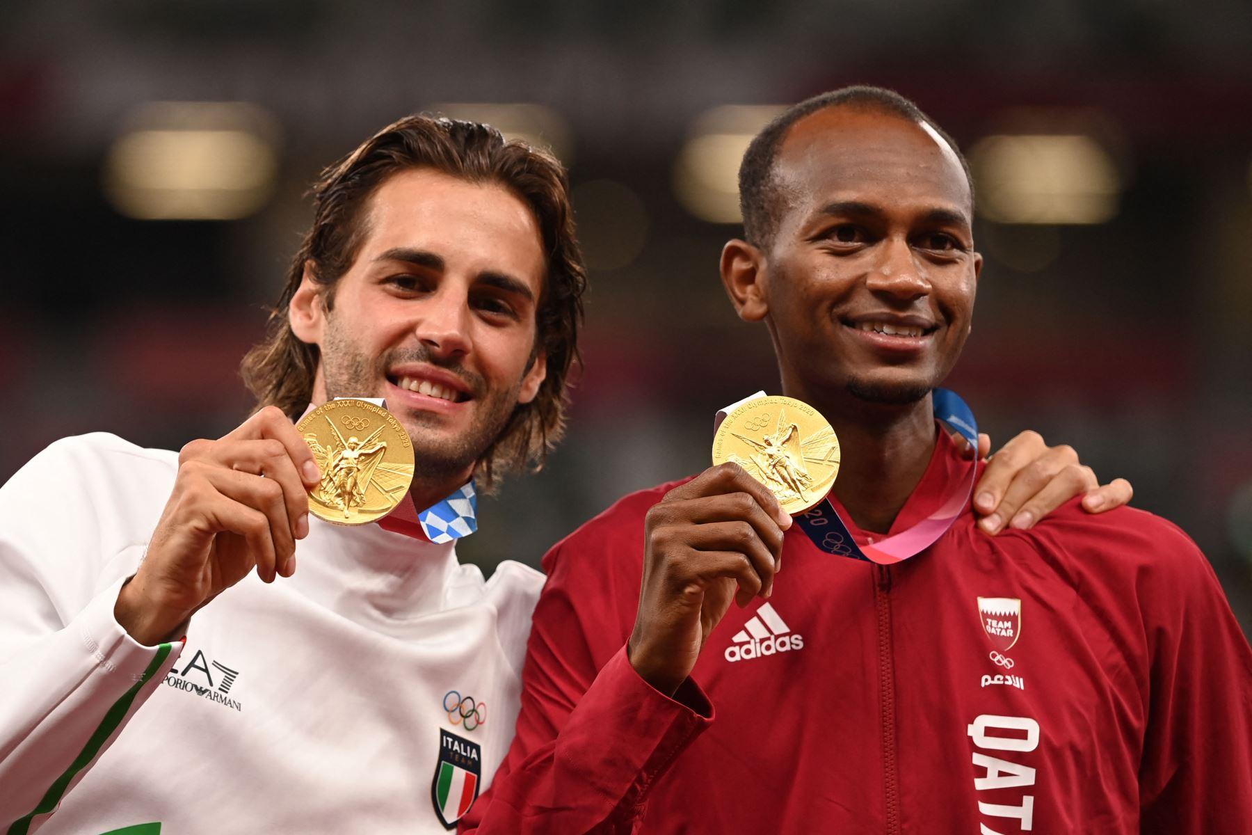 Los medallistas de oro conjuntos Mutaz Essa Barshim de Qatar y Gianmarco Tamberi de Italia posan en el podio de la final masculina de salto de altura durante los Juegos Olímpicos de Tokio 2020 en el Estadio Olímpico de Tokio. Foto: AFP