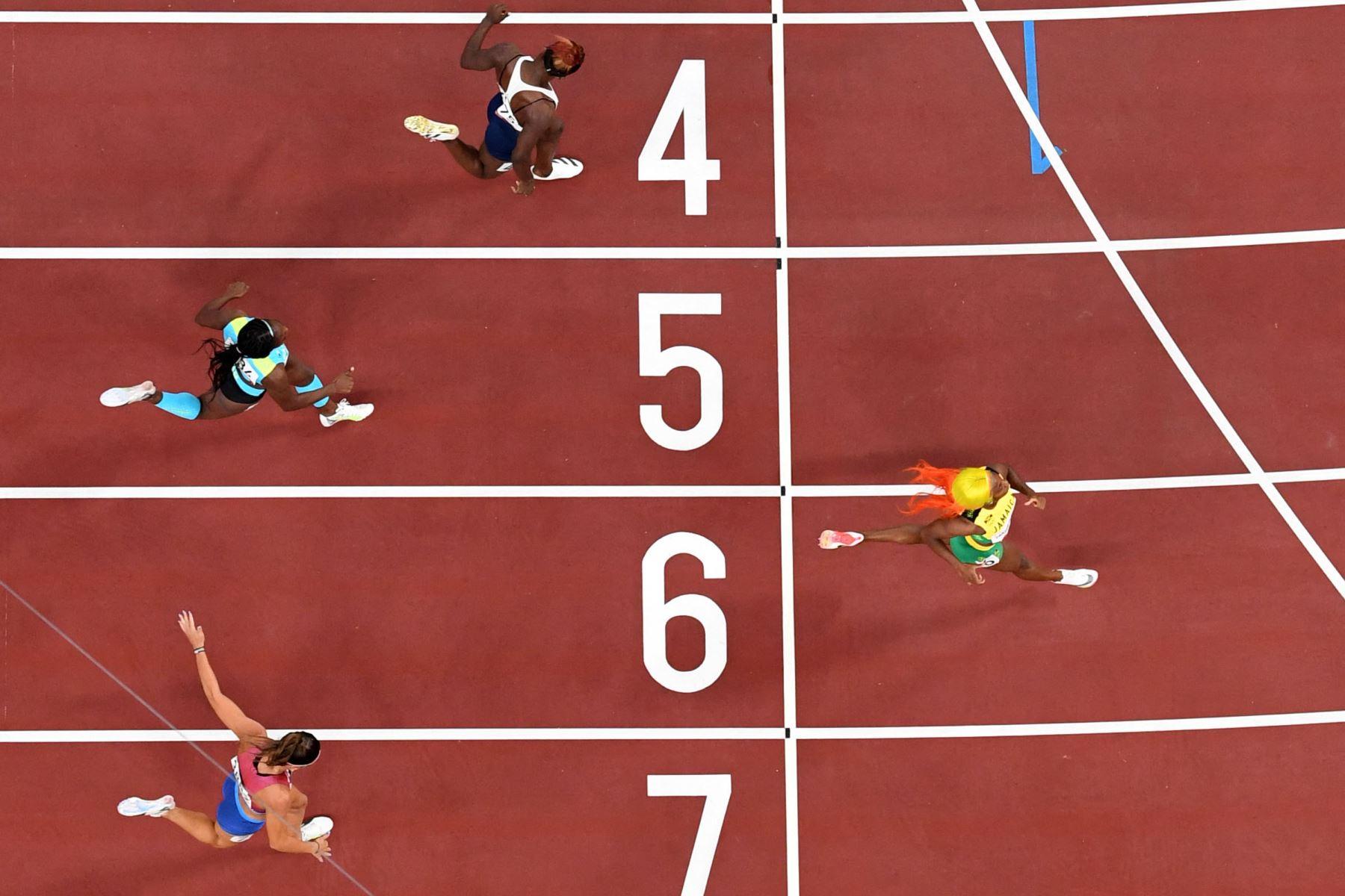 Shelly-Ann Fraser-Pryce de Jamaica gana las semifinales femeninas de 200 metros flanqueada por la estadounidense Jenna Prandini, Anthonique Strachan de Bahamas y Beatrice Masilingi de Namibia (ARRIBA) durante los Juegos Olímpicos de Tokio 2020 en el estadio olímpico de Tokio. Foto: AFP