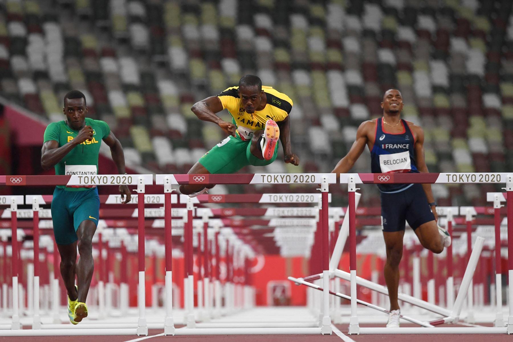 Gabriel Constantino (L) de Brasil, Ronald Levy (C) de Jamaica y Wilhem Belocian (R) de Francia compiten en las eliminatorias masculinas de 110 metros con vallas durante los Juegos Olímpicos de Tokio 2020.  Foto: AFP
