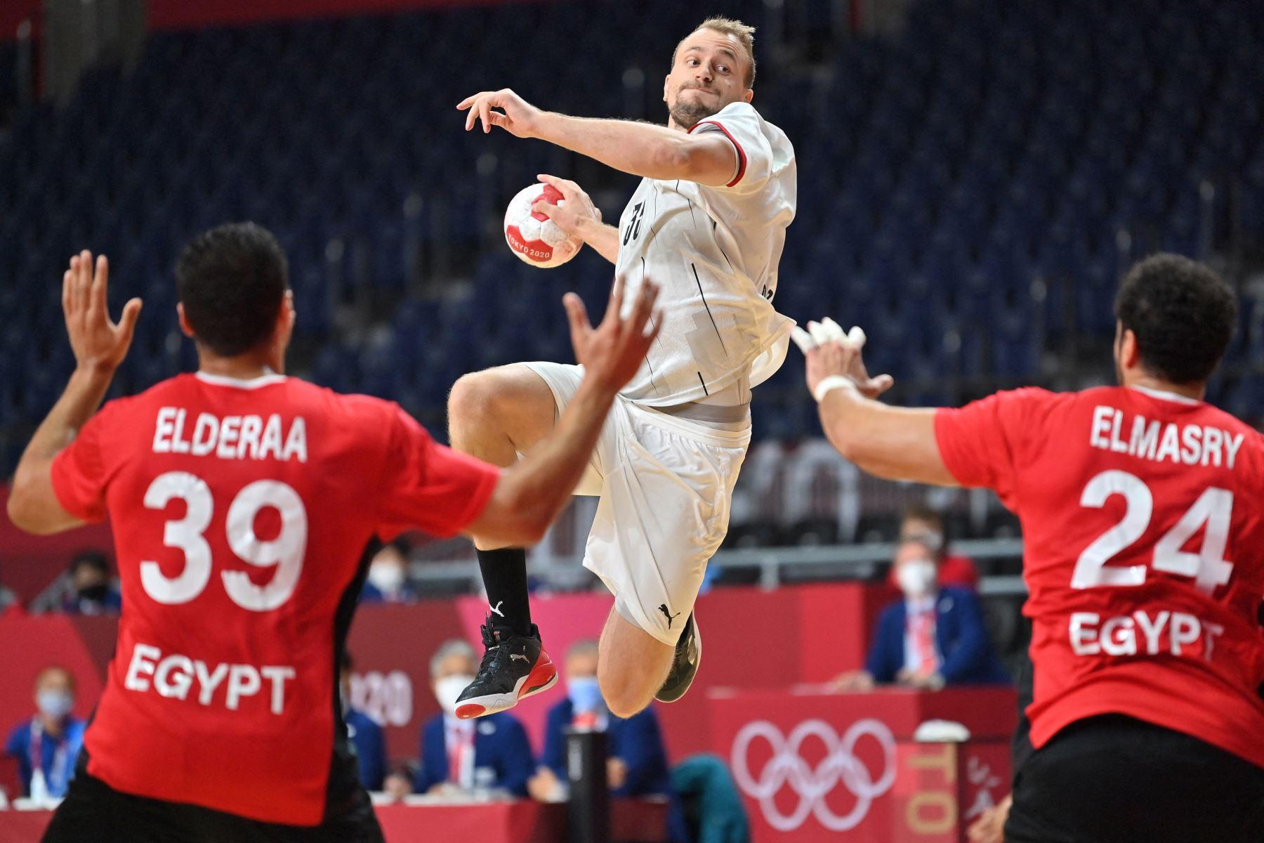 El lateral izquierdo alemán Julius Kuhn (C) salta para disparar durante el partido de balonmano masculino de cuartos de final entre Alemania y Egipto de los Juegos Olímpicos de Tokio 2020.  Foto: AFP