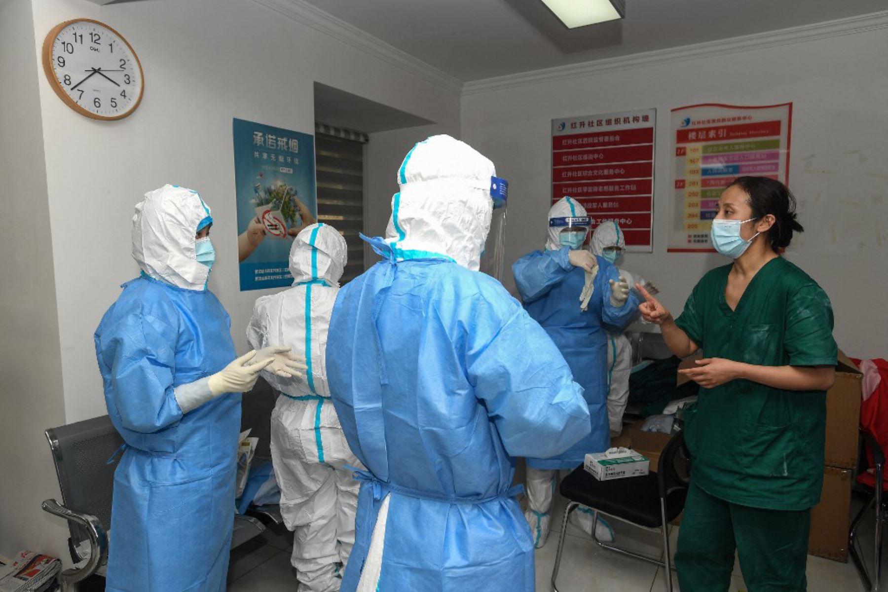 Los miembros del personal médico tienen una reunión mientras se preparan para realizar pruebas de ácido nucleico para detectar el coronavirus en Wuhan, en la provincia central de Hubei, en China  Foto:AFP