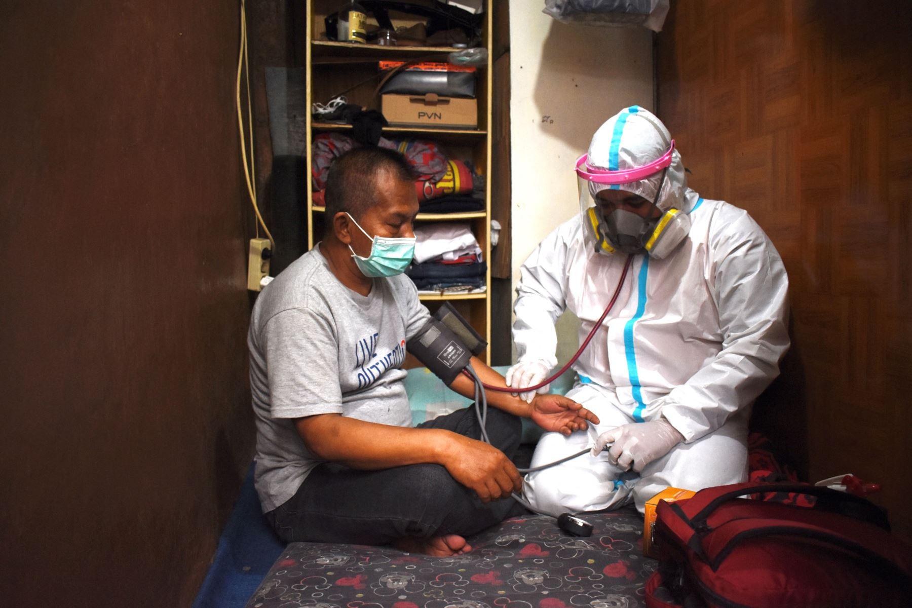 Un trabajador de salud controla a un residente que se aísla por sí mismo durante la pandérmica del coronavirus en su casa en Bandung. Foto: AFP