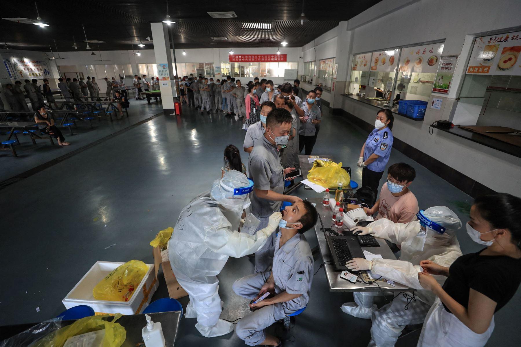 Un trabajador recibe una prueba de ácido nucleico para el covid-19 en el comedor de una fábrica de piezas de automóviles en Wuhan, en la provincia central de Hubei, China. Foto: AFP