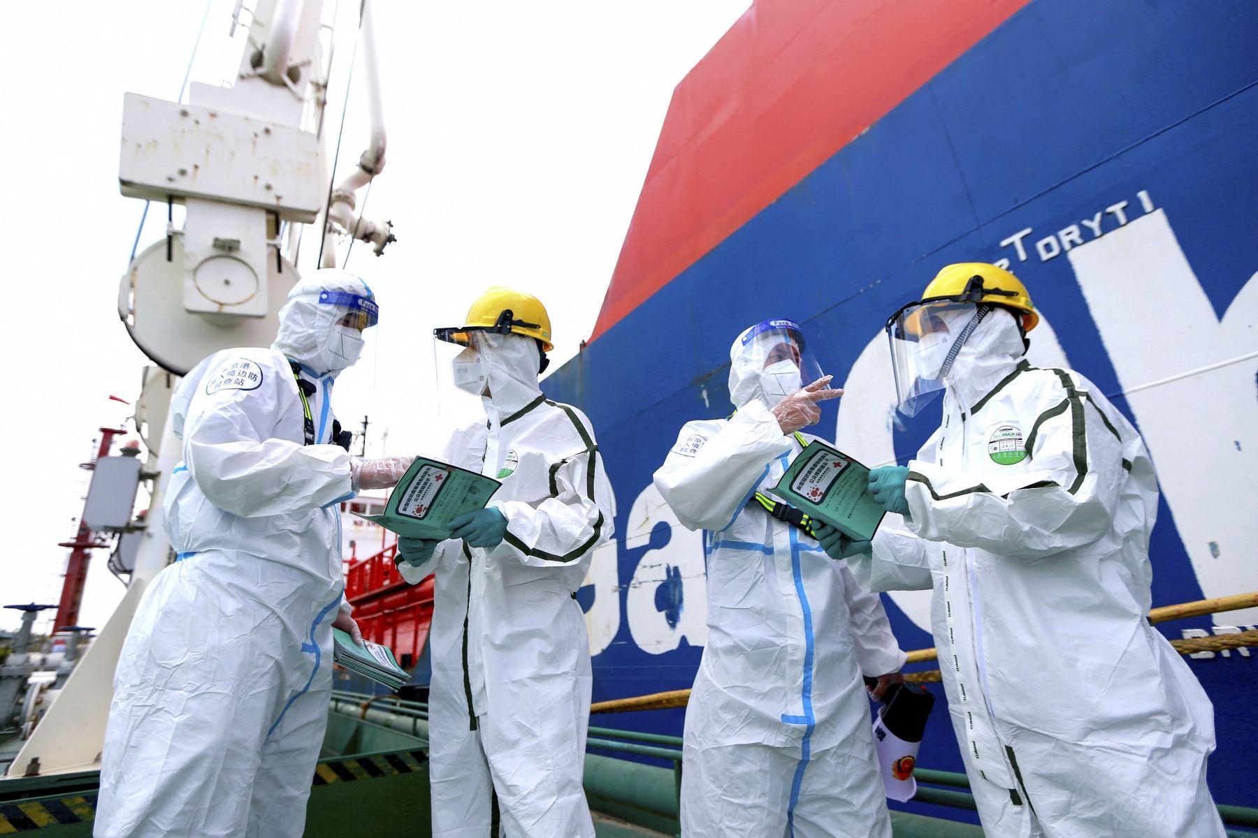 Los agentes de policía con equipo de protección explican la información de prevención de la pandemia para luchar contra la propagación del covid-19 a los trabajadores en el puerto de Nanjing, en la provincia de Jiangsu, en el este de China. Foto: AFP