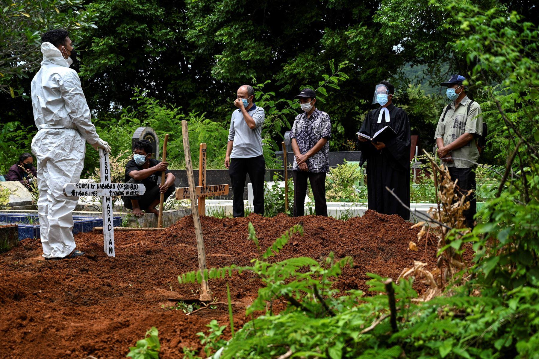 Familiares rezan después de bajar el ataúd de una víctima del coronavirus en un cementerio en Darul Imarah, en las afueras de Banda Aceh. Foto: AFP