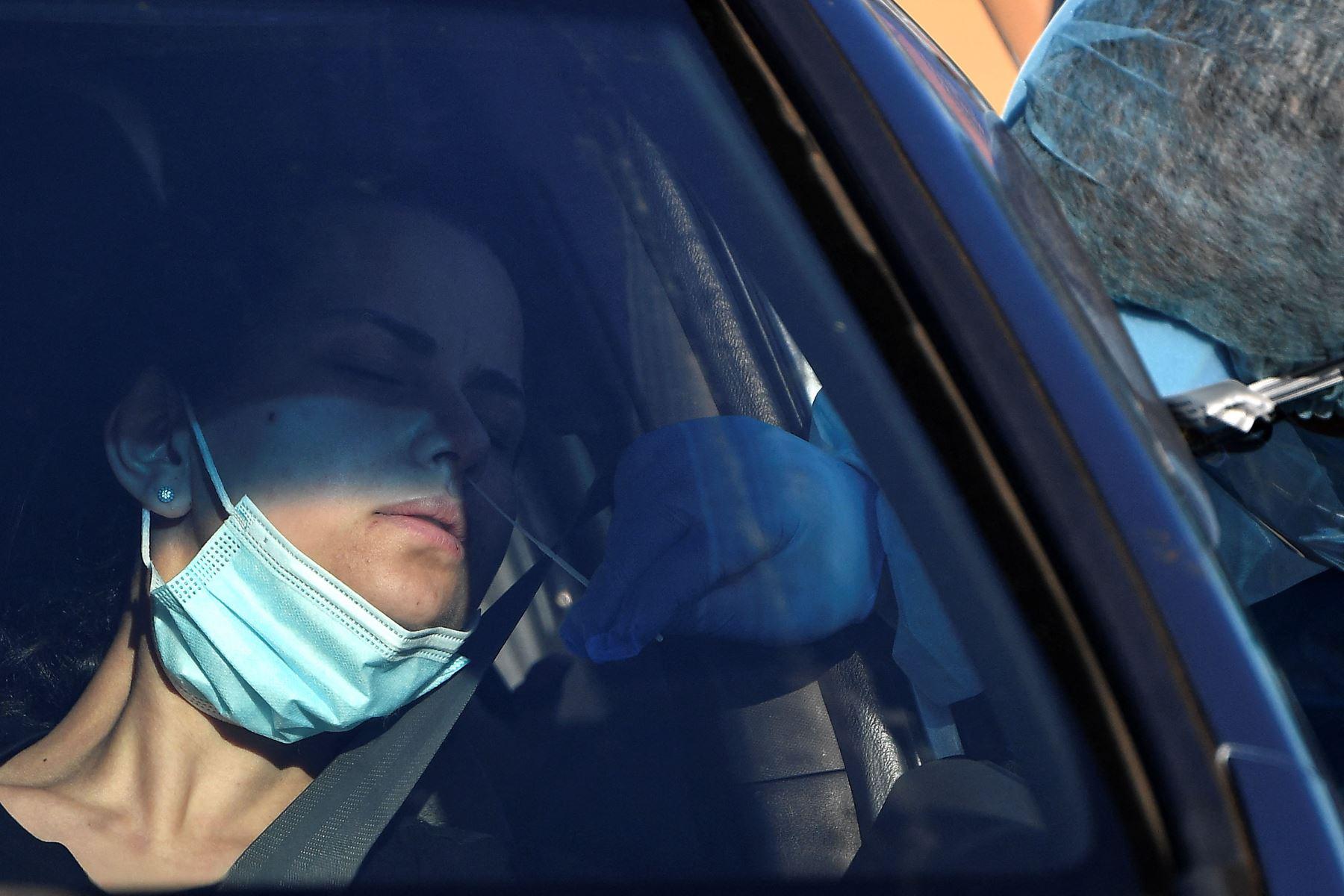 Un trabajador de la salud  toma una muestra de un hisopo de un residente en un sitio de prueba covid-19 en el oeste de Sydney. Foto: AFP
