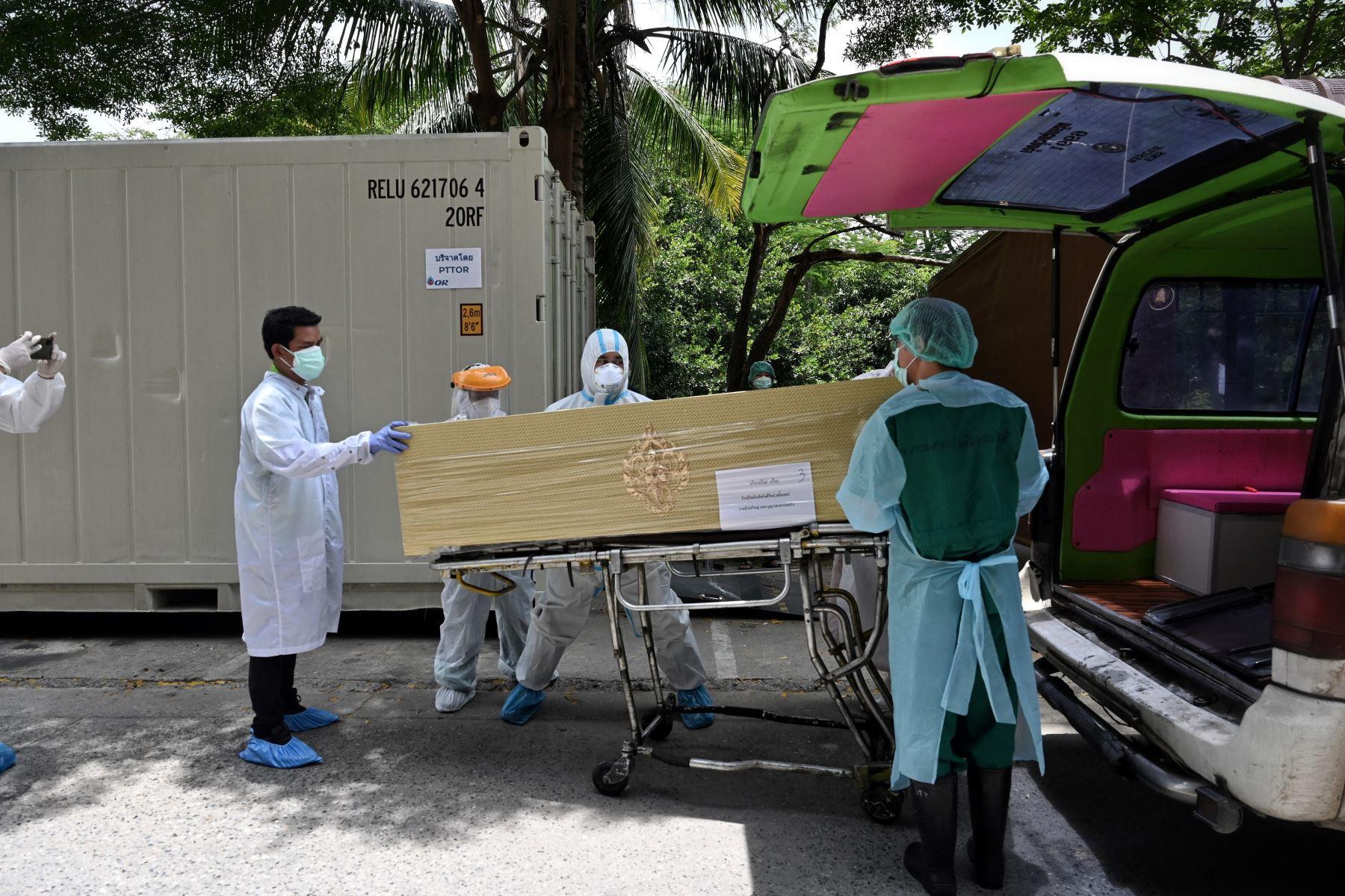 Los trabajadores del hospital trasladan a las víctimas del coronavirus de un contenedor de almacenamiento refrigerado a ataúdes fuera de la morgue del Hospital Thammasat en la provincia de Pathum Thani, al norte de Bangkok. Foto: AFP
