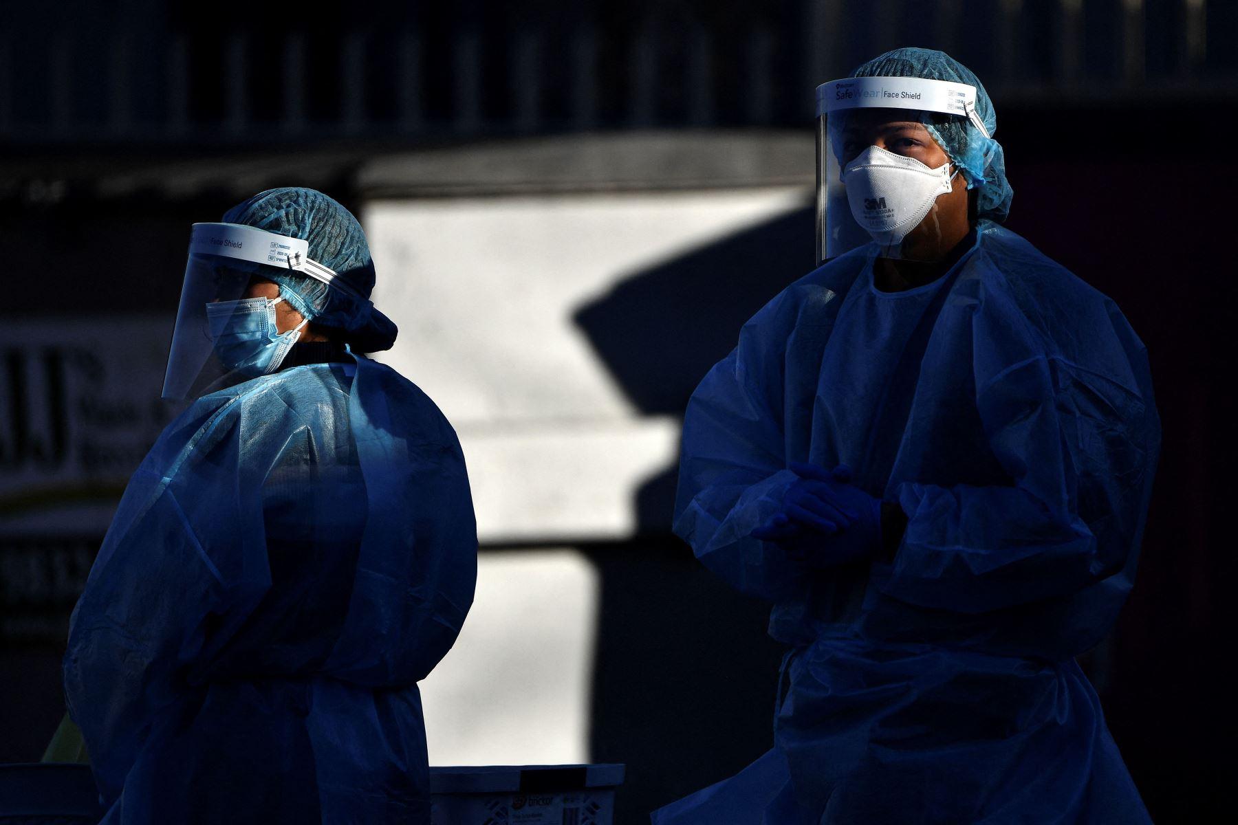 Los trabajadores de la salud esperan a que los residentes tomen muestras de hisopos en un sitio de prueba de covid-19 en el oeste de Sydney. Foto: AFP