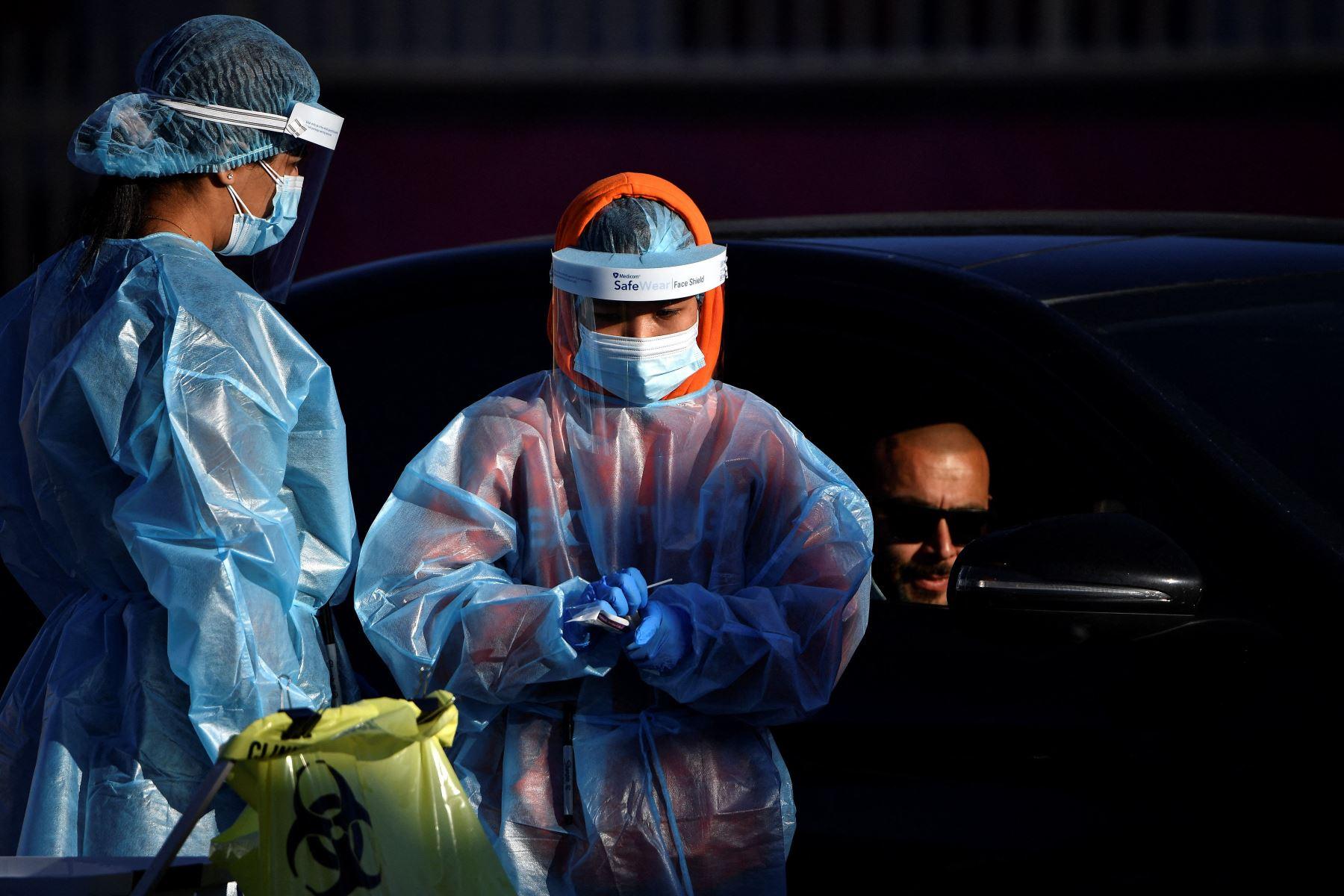 Los trabajadores de la salud toman muestras de hisopos de los residentes en un sitio de prueba covid-19 en el oeste de Sydney. Foto: AFP