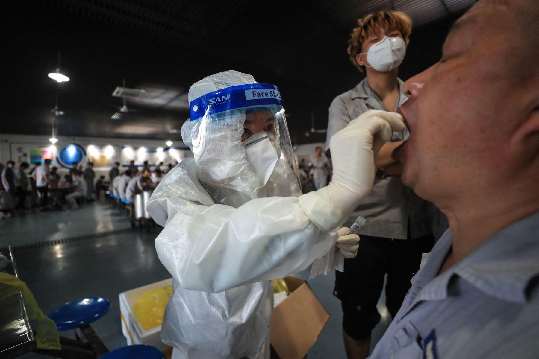 Un trabajador recibe una prueba de ácido nucleico para el coronavirus  en el comedor de una fábrica de piezas de automóviles en Wuhan, en la provincia central de Hubei, China. Foto: AFP