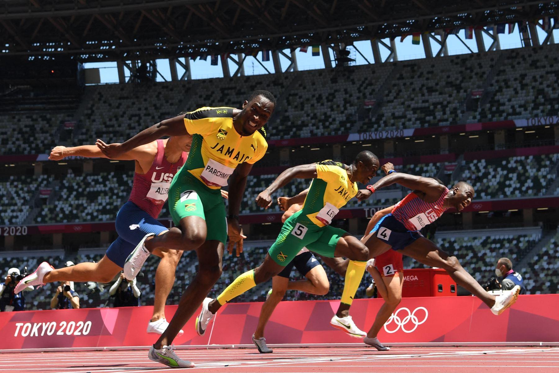 Hansle Parchment de Jamaica cruza la línea de meta para ganar por delante del segundo clasificado de Estados Unidos Grant Holloway  y el tercer clasificado de Jamaica Ronald Levy en la final masculina de 110 metros con vallas, durante los Juegos Olímpicos de Tokio 2020 en el estadio Olímpico de Tokio. FOTO:AFP