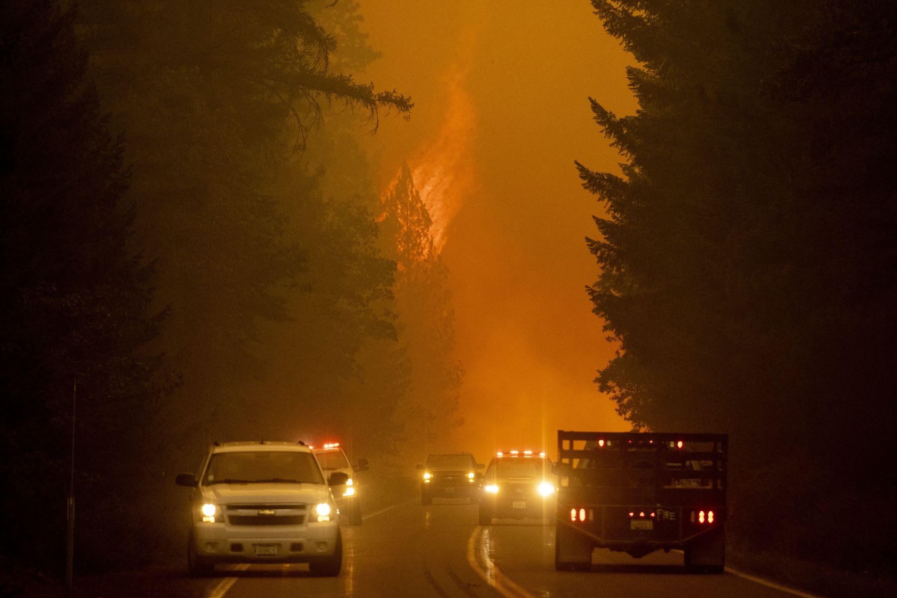 Los bomberos monitorean la escena mientras las llamas del incendio de Dixie saltan a través de la autopista 89 cerca de Greenville, California. Foto: AFP