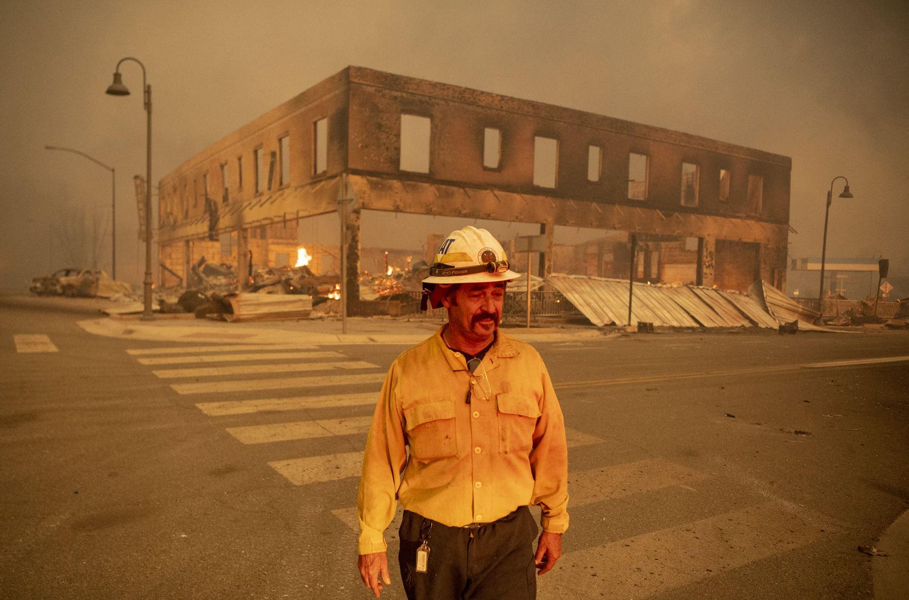 El jefe del batallón Sergio Mora observa mientras el incendio de Dixie arde en el centro de Greenville, California. El incendio de Dixie arrasó decenas de hogares y negocios en el centro de Greenville. Foto: AFP