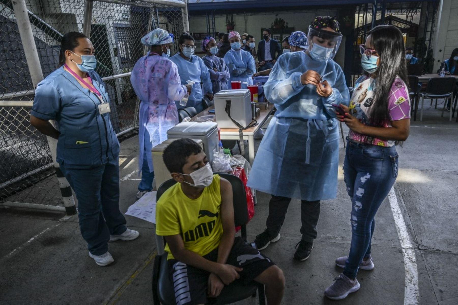 Una enfermera muestra una dosis de la vacuna Pfizer-BioNtech covid-19 a una madre antes de vacunar a un niño en una escuela en Medellín, Colombia. Foto: AFP