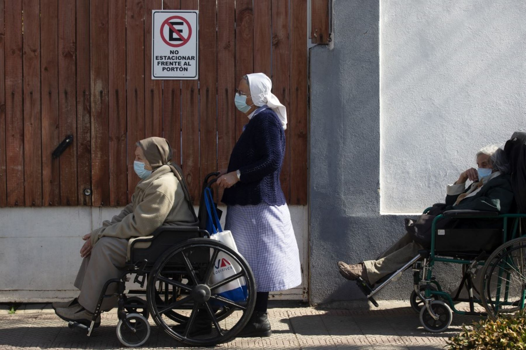 Ancianos hacen cola esperando su turno para recibir una tercera dosis de refuerzo de la vacuna Astrazeneca contra Covid-19 en un centro de vacunación de Santiago de Chile. Foto: AFP