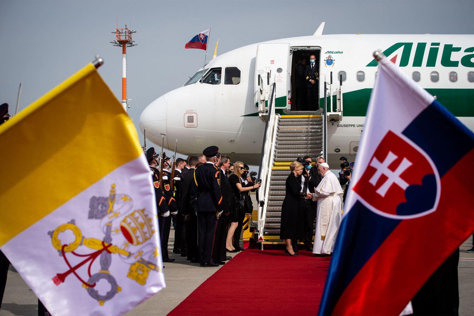 La presidenta eslovaca Zuzana Caputova y el papa Francisco se dan la mano frente a un avión de Alitalia antes de la salida del pontífice del aeropuerto internacional Milan Rastislav Stefanik de Bratislava en  Eslovaquia. Foto: AFP