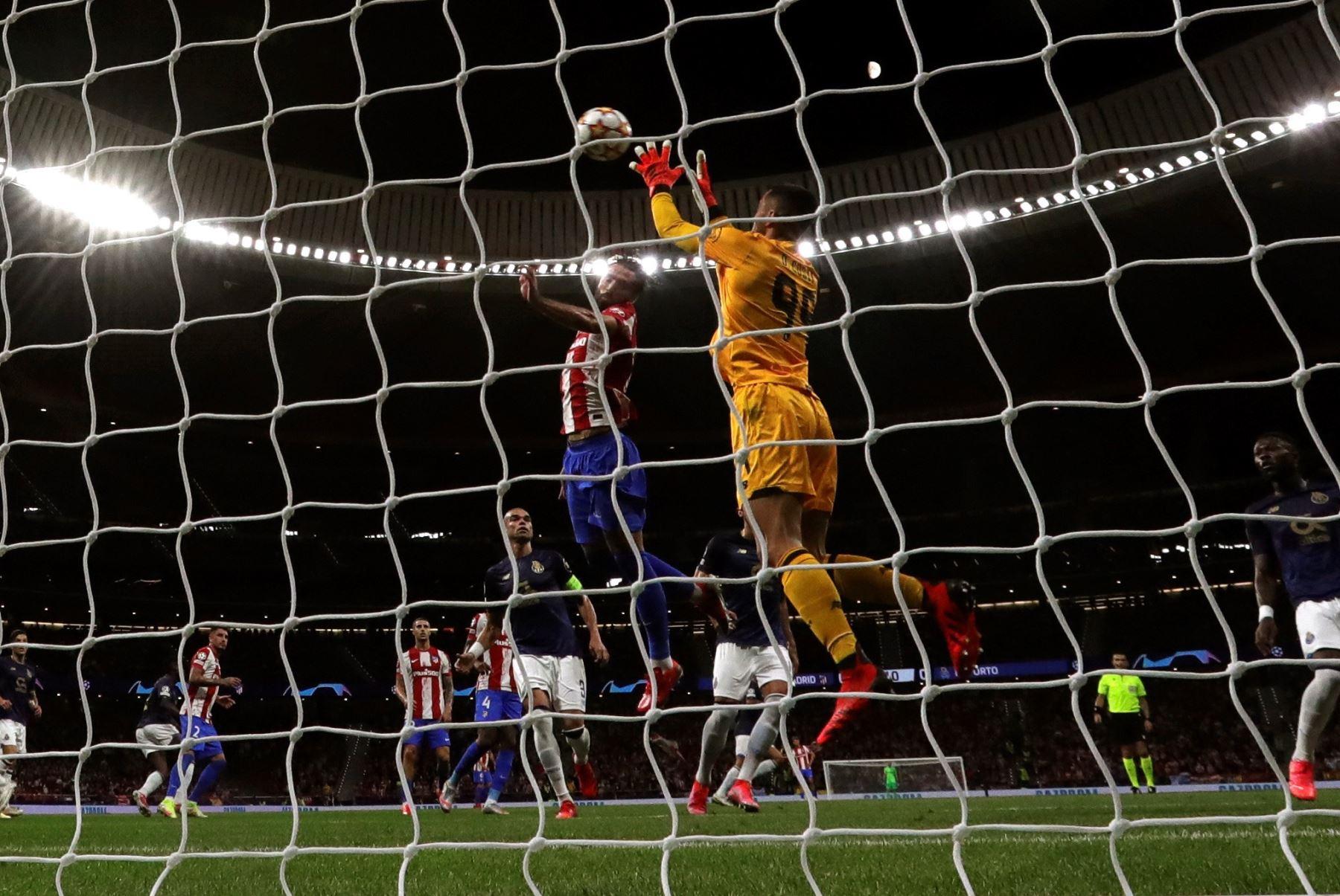 El portero del Oporto Diogo Costa detiene un balón ante Felipe Monteiro, del Atlético de Madrid, que disputan este miércoles en el Wanda Metropolitano. EFE/Juanjo Martín