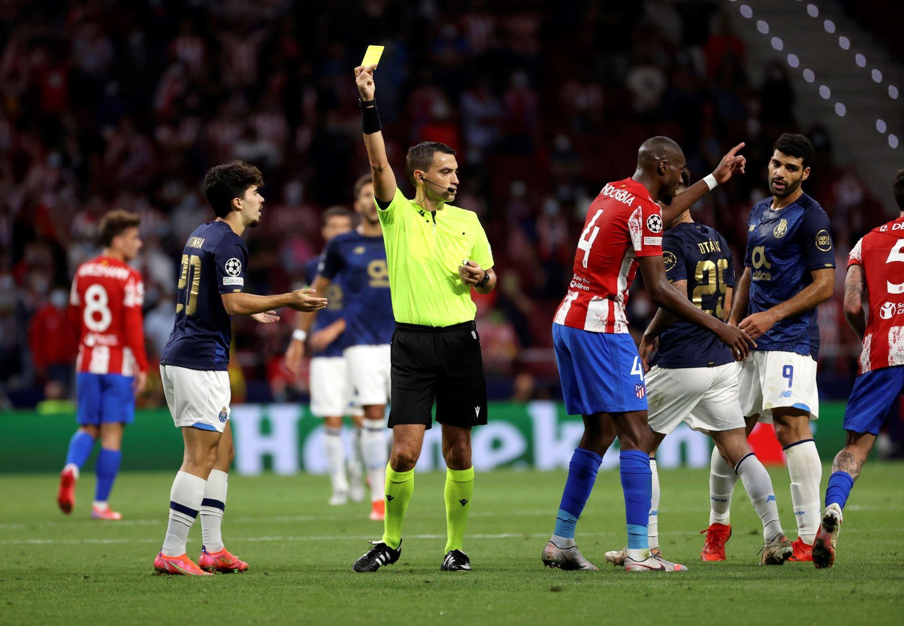 El árbitro Ovidiu Hategan muestra tarjeta amarilla a Vitor Ferreira, del Oporto, durante el partido de la primera jornada. EFE/Juanjo Martín