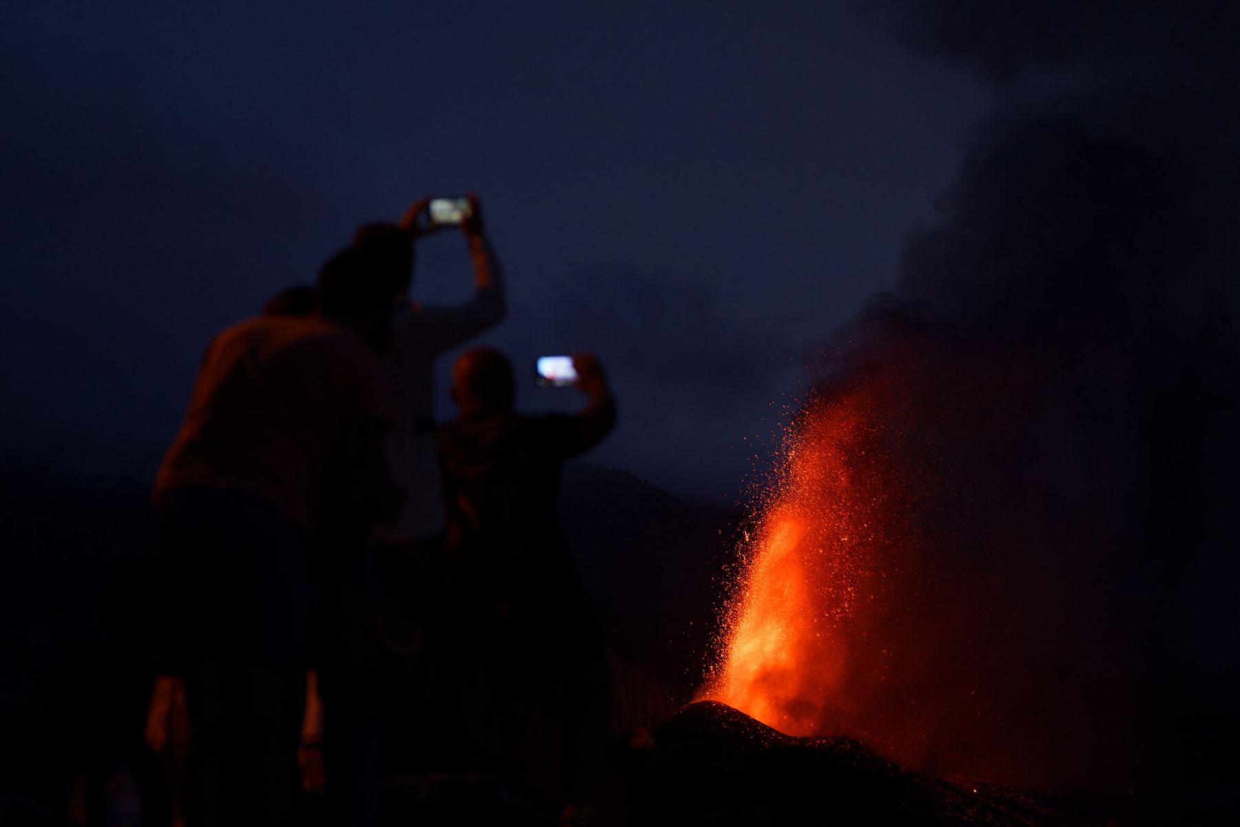 Cuatro personas contemplan desde una montaña al caer la noche la lava que sale proyectada hacia el cielo del nuevo volcán de La Palma. Foto: EFE