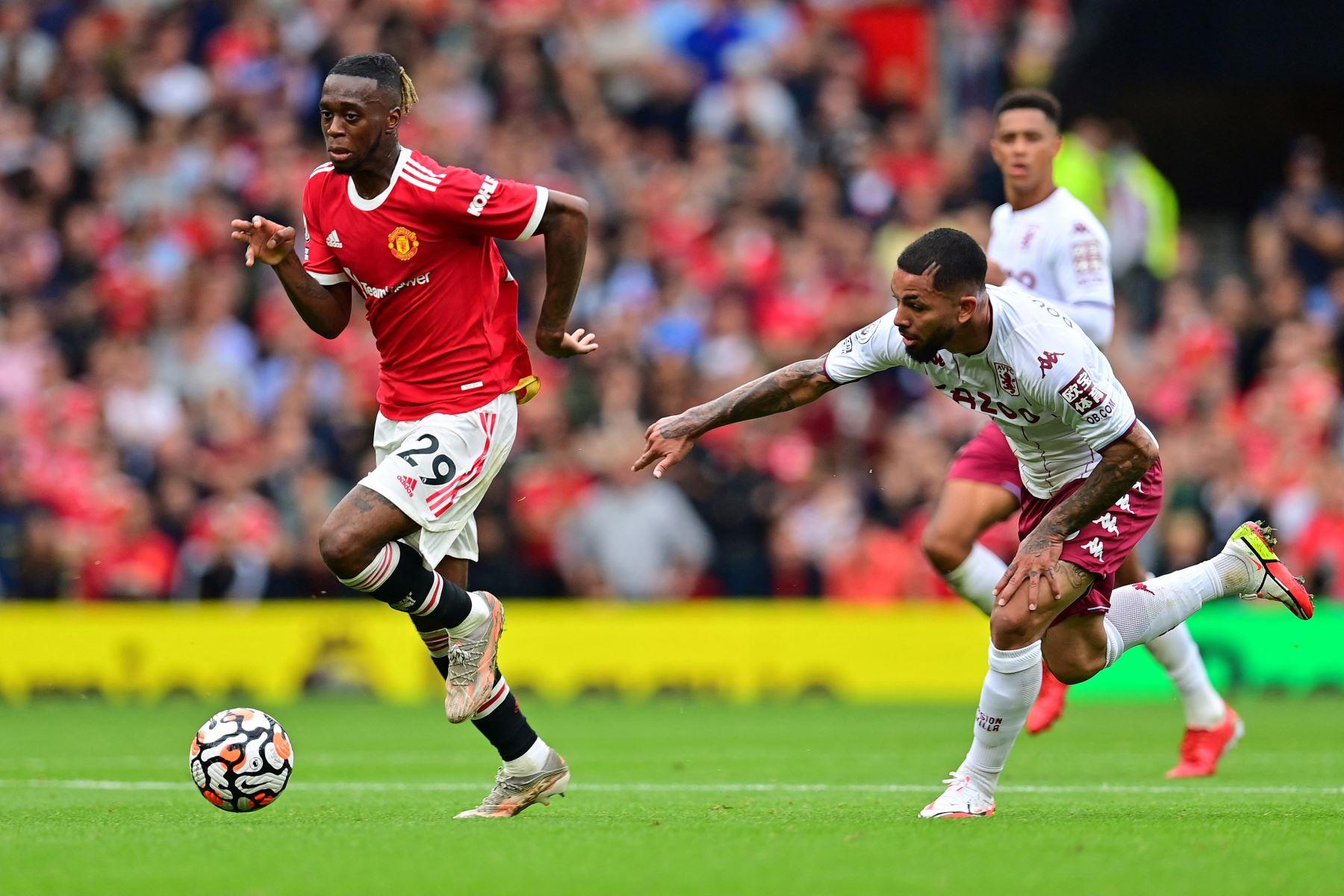 El defensor inglés del Manchester United Aaron Wan-Bissaka supera al mediocampista brasileño del Aston Villa Douglas Luiz durante el partido de fútbol de la Premier League inglesa entre el Manchester United y el Aston Villa. Foto: AFP